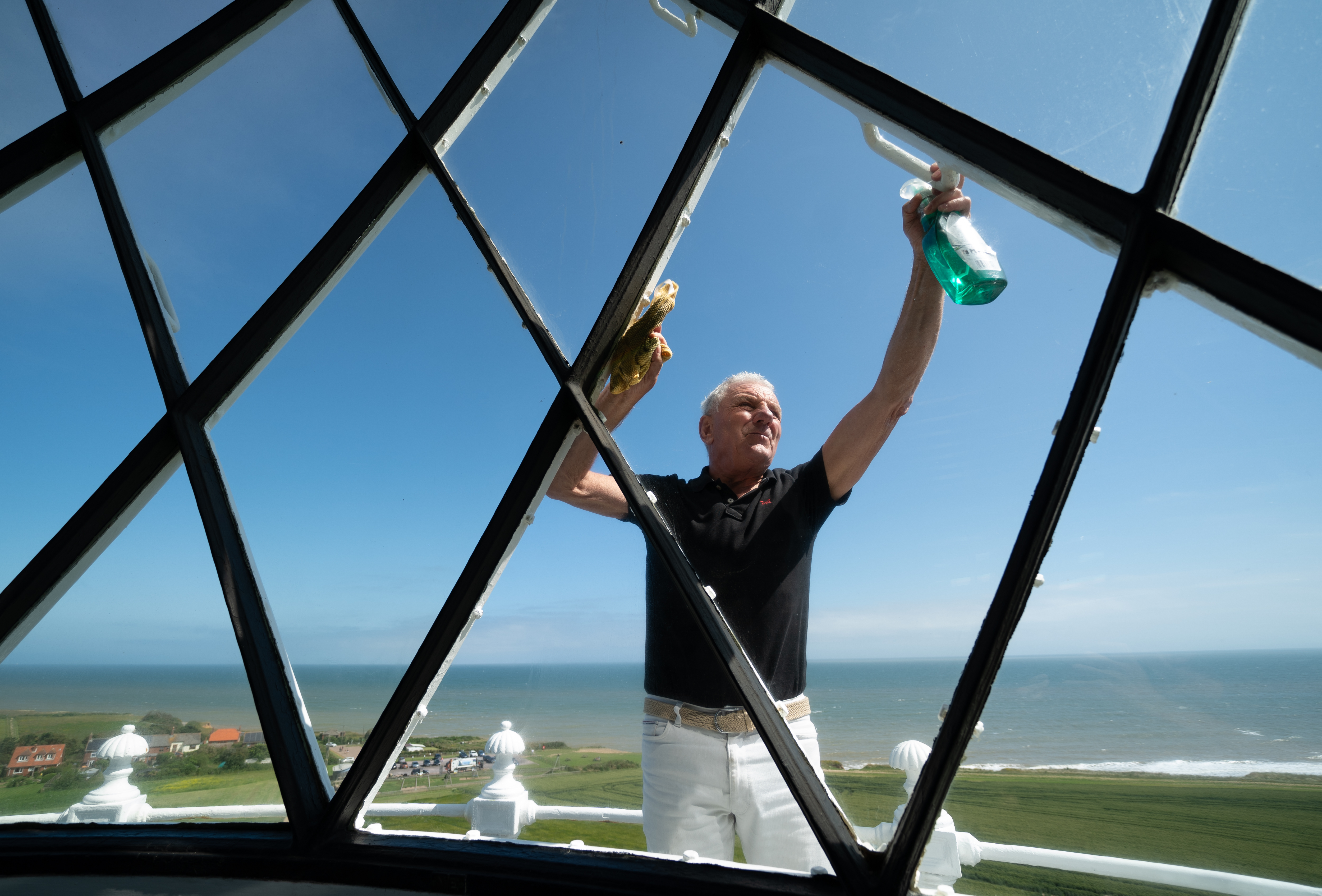 <p>Chairman of Friends of Happisburgh Lighthouse David Vyse cleans the windows on the lantern room of Happisburgh Lighthouse in Norfolk as it prepares to reopen to visitors after being closed since 2019 due to the Coronavirus pandemic. Picture date: Thursday July 15, 2021.</p>