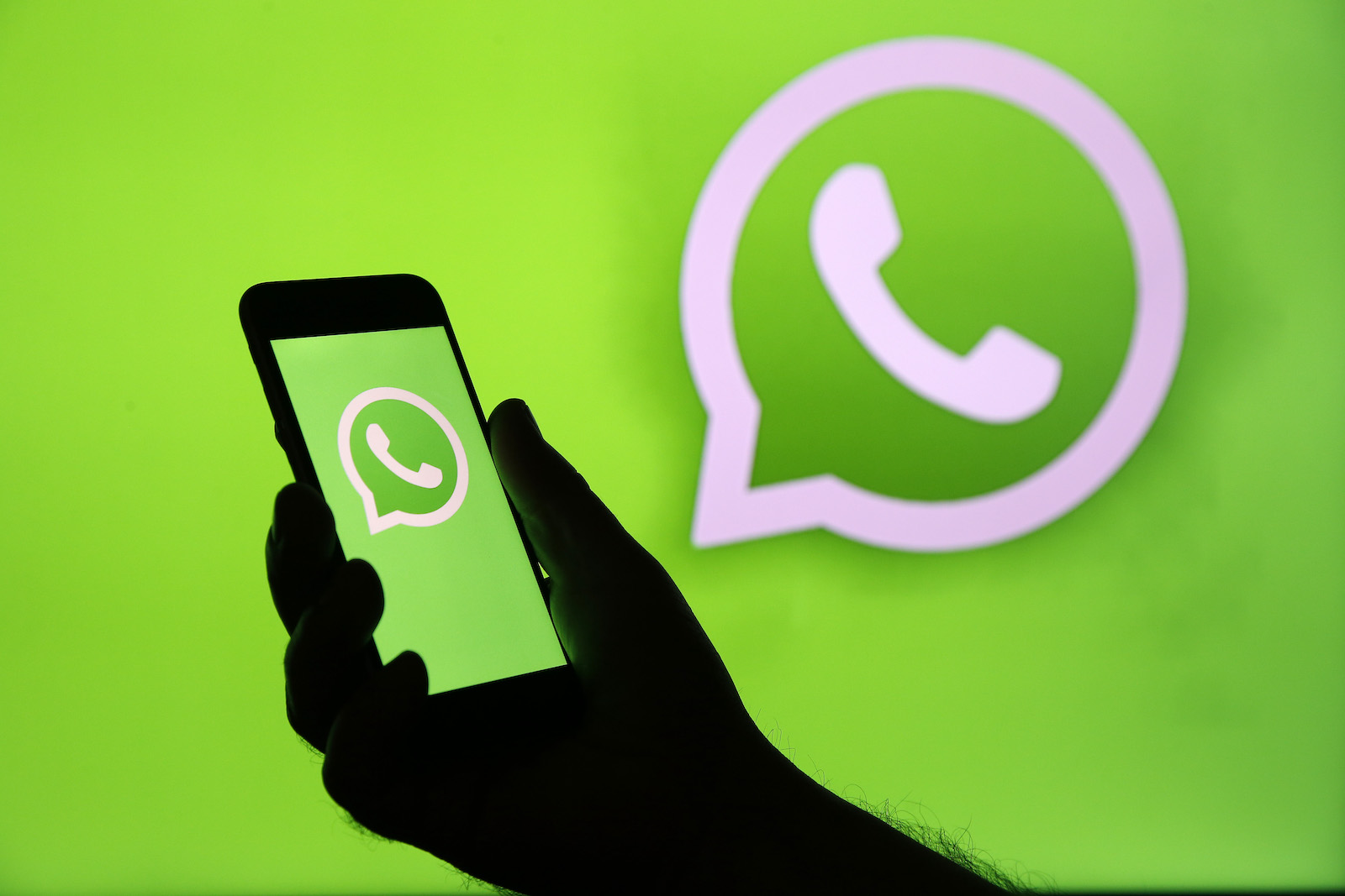 PARIS, FRANCE - DECEMBER 10: In this photo illustration, the WhatsApp logo is displayed on the screen of an iPhone in front of a TV screen displaying the WhatsApp logo on December 10, 2019 in Paris, France. The WhatsApp instant messenger service will stop working on millions of phones in the next couple of months as the company withdraws support for some older mobile platforms. From February 1, 2020, any iPhone running iOS 8 or older will no longer be supported, along with any Android device running version 2.3.7 or older. (Photo by Chesnot/Getty Images)