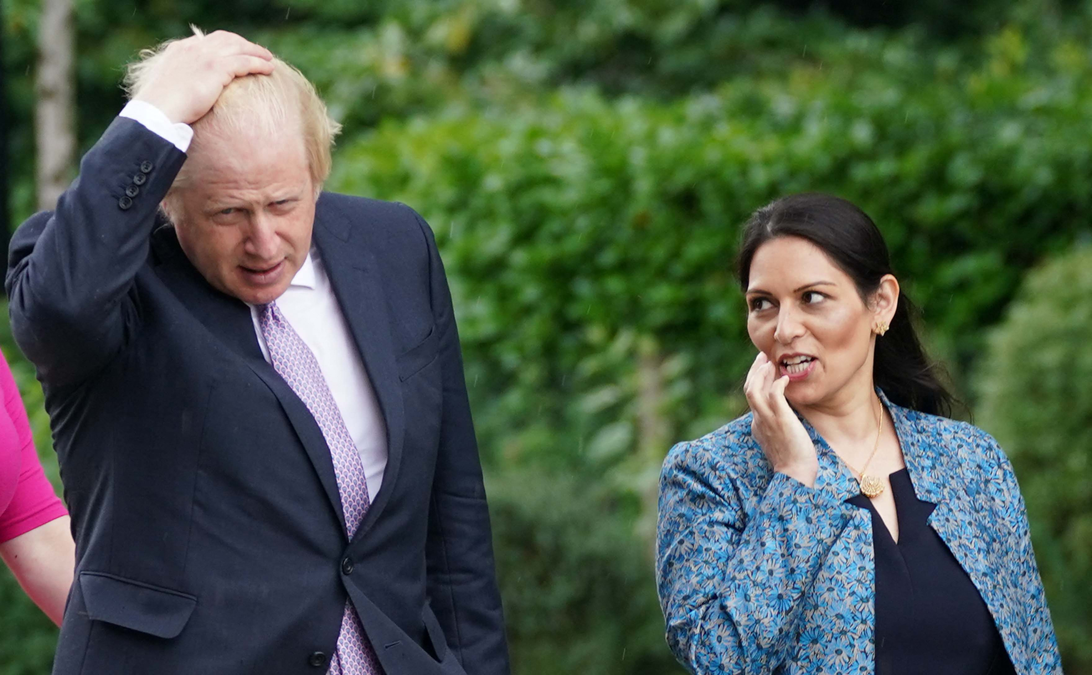 <p>Britain's Prime Minister Boris Johnson (L) and Britain's Home Secretary Priti Patel (R) visit to Surrey Police headquarters in Guildford, south west of London, on July 27, 2021 to coincide with the publication of the government's plans to tackle crime. (Photo by Yui Mok / POOL / AFP) (Photo by YUI MOK/POOL/AFP via Getty Images)</p>