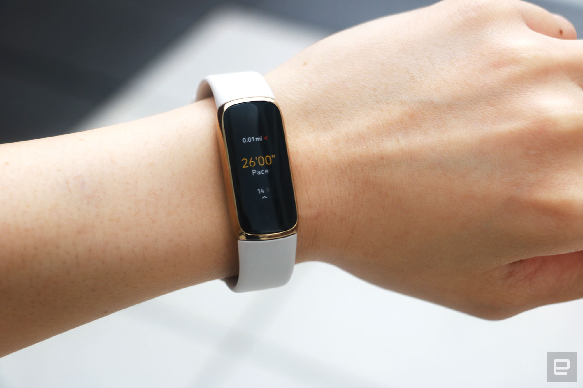 <p>The Fitbit Luxe with a light pink silicone band on a wrist against a concrete gray background. The screen shows a run being tracked with a pace of 26:00 and 0.01 miles traveled.</p>