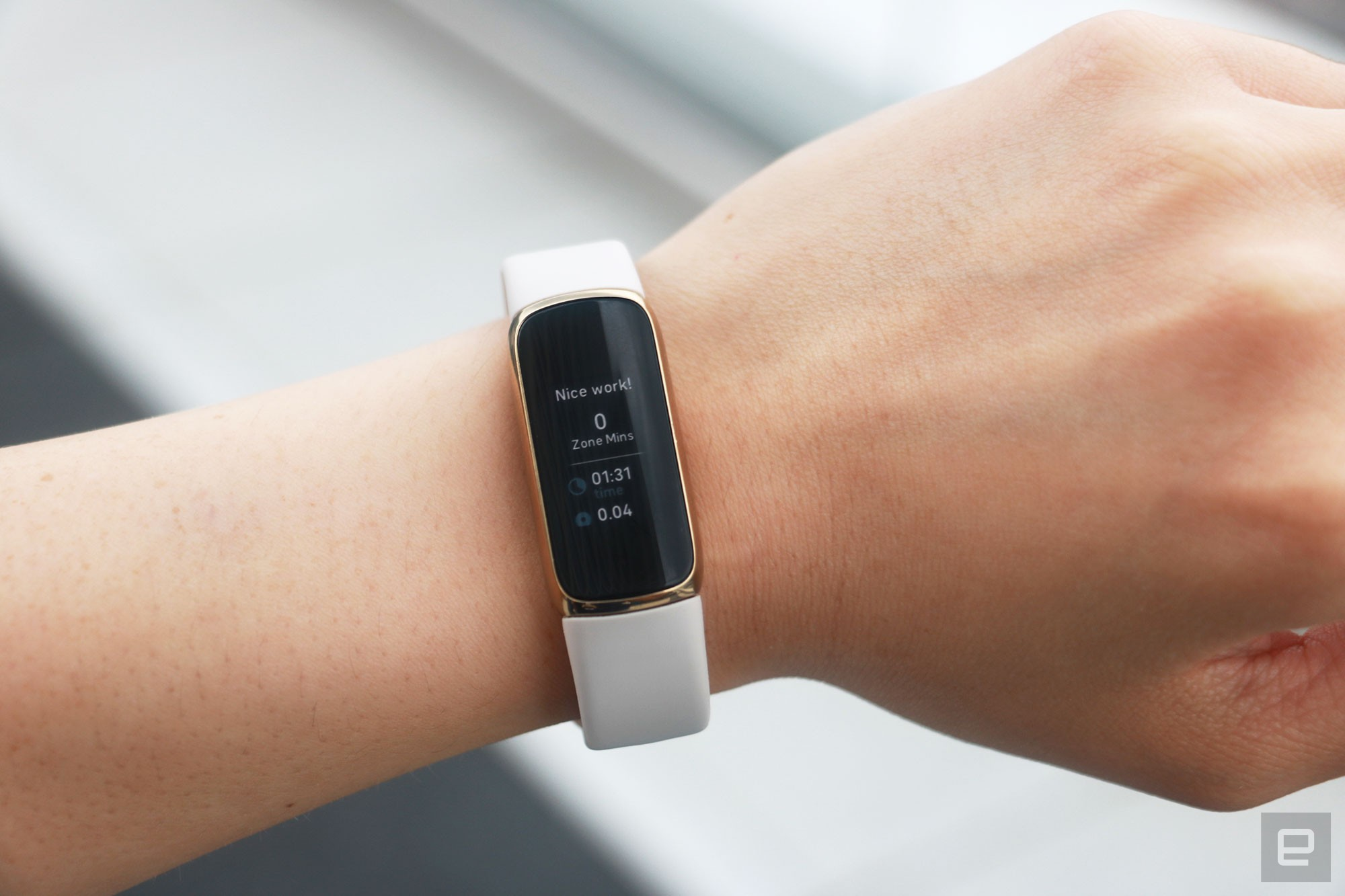 """<p>The Fitbit Luxe with a light pink silicone band on a wrist facing the camera. The screen shows a post workout report saying """"Nice work!"""" with results including 0 zone minutes earned and 1 minute and 31 seconds spent covering 0.04 miles.</p>"""
