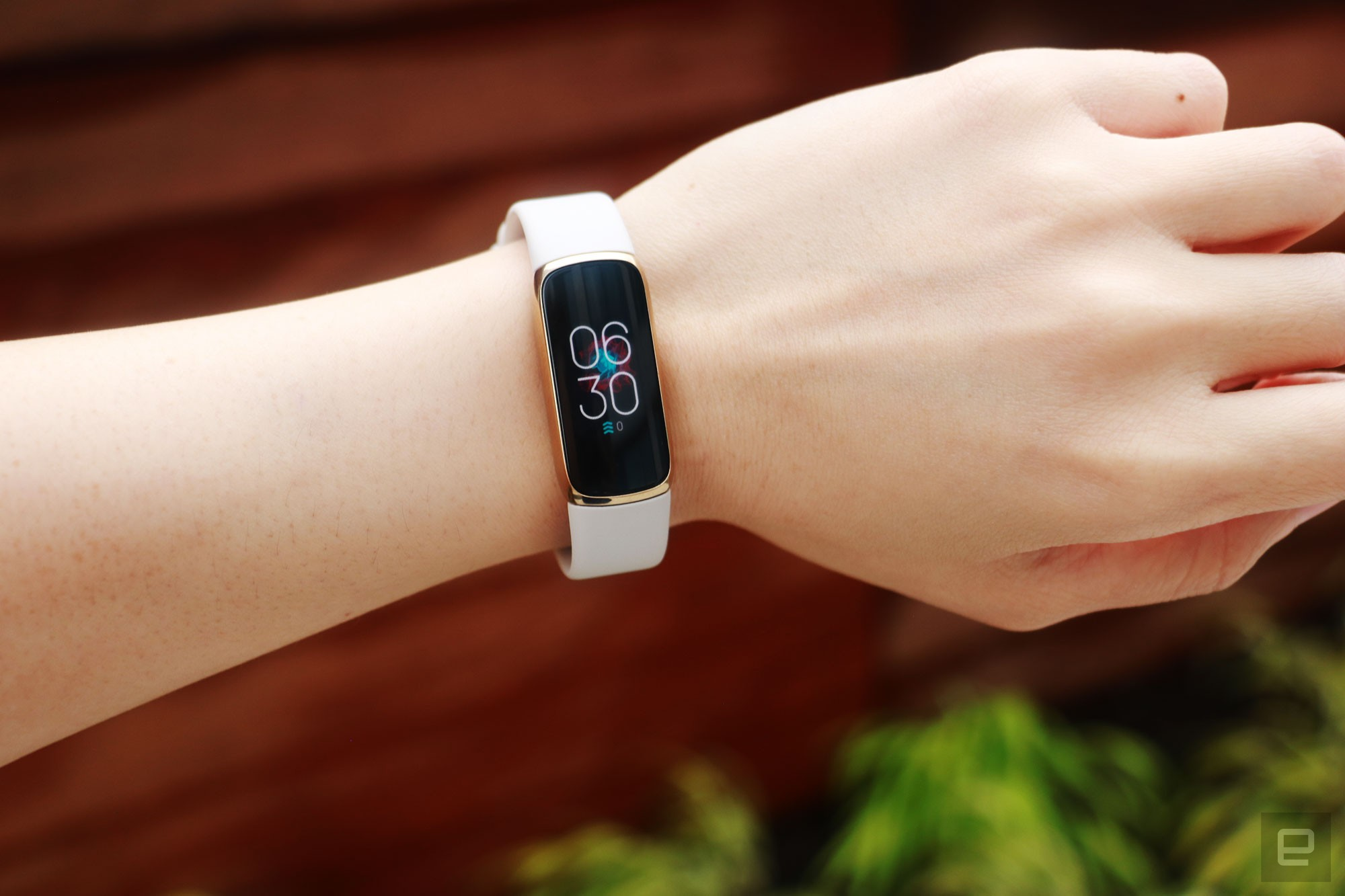 <p>Front view of the Fitbit Luxe with a light pink silicone band on a wrist against a dark brown background with some greenery. The screen shows the time is 6:30pm.</p>