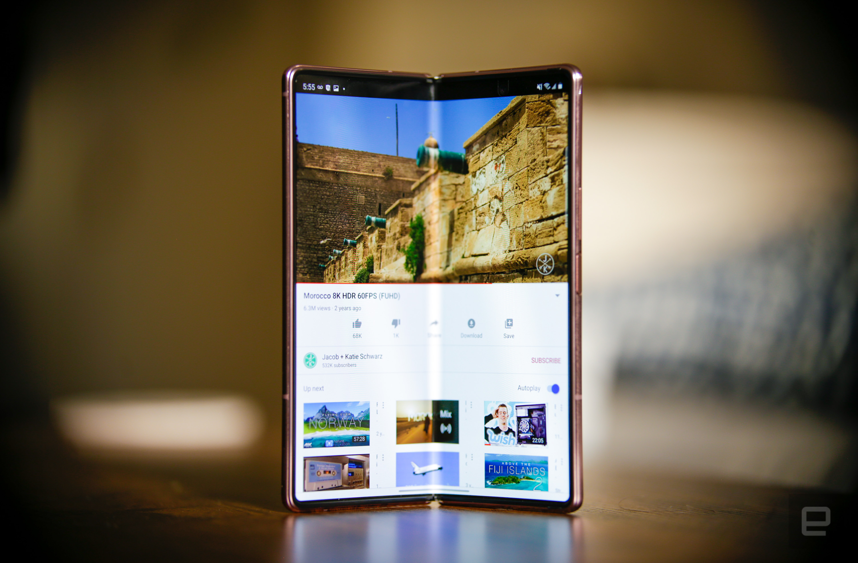 The Samsung Galaxy Z Fold 2 standing in portrait orientation on a wooden table with its screen partly folded and facing the camera. It shows a YouTube video playing.