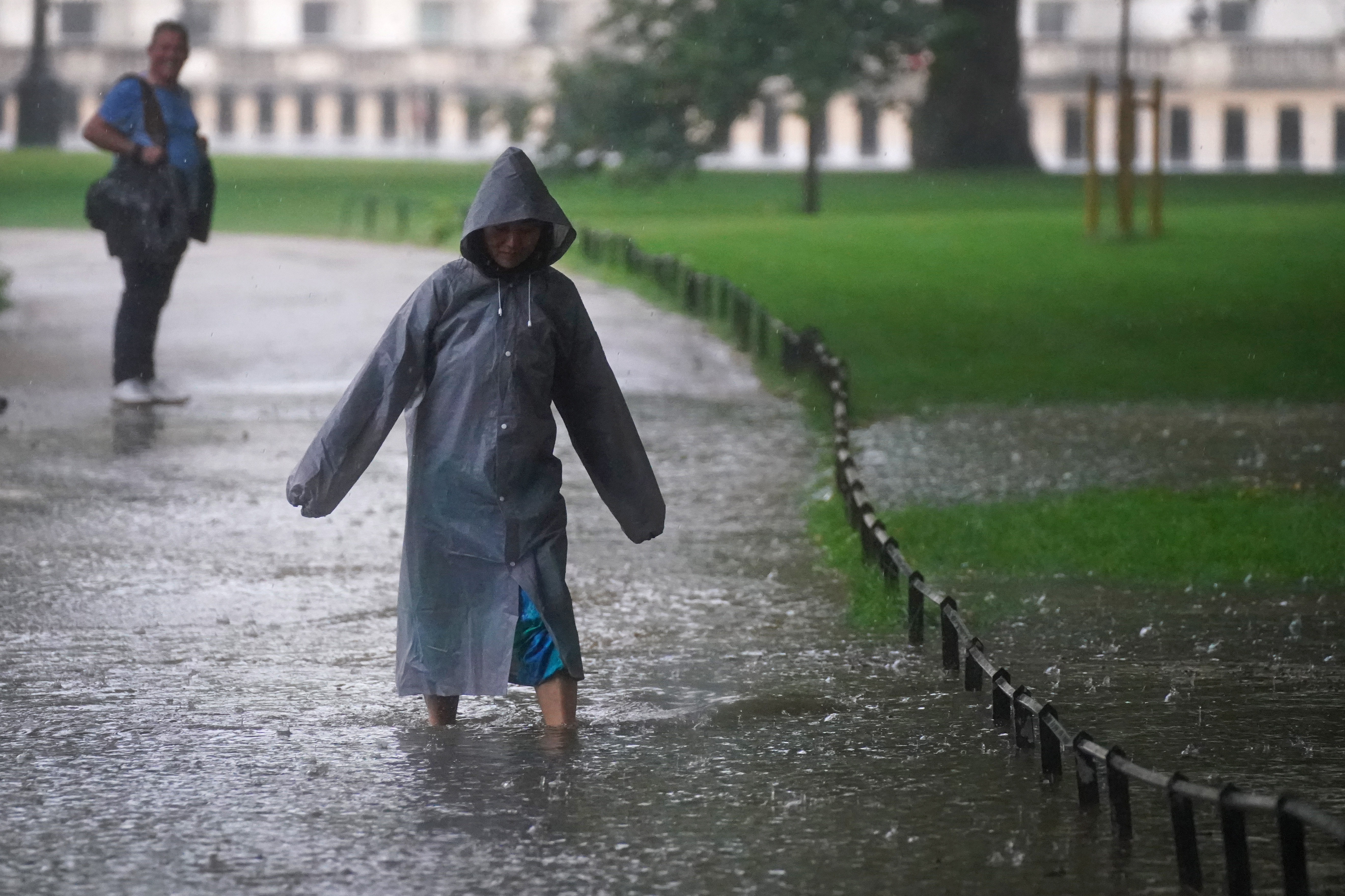 <p>A woman walks through a flooded path in St James's Park in central London. Thunderstorms bringing lightning and torrential rain to the south are set to continue until Monday, forecasters have said. Picture date: Sunday July 25, 2021.</p>