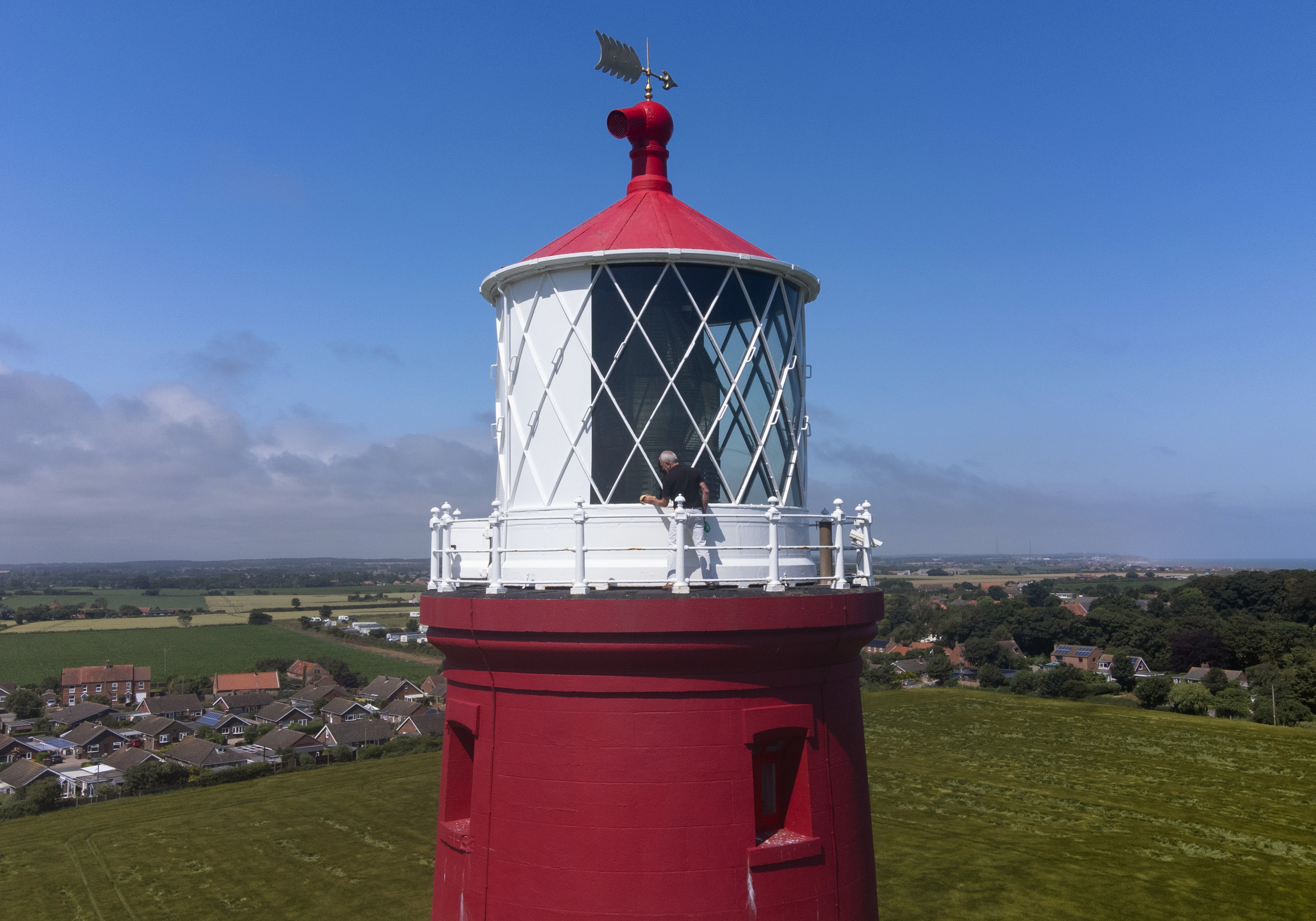 <p>The windows on the lantern room are cleaned at Happisburgh Lighthouse in Happisburgh on the North Norfolk coast as it prepares to reopen to visitors after being closed since 2019 due to the Coronavirus pandemic. Picture date: Thursday July 15, 2021.</p>