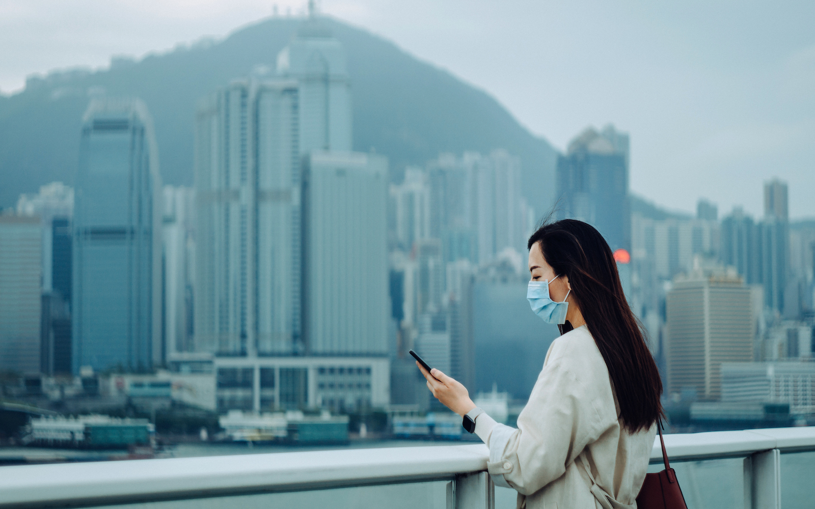 Young Asian woman with surgical face mask   to prevent the spread of viruses during the Covid-19 health crisis and using smartphone against the iconic city skyline of Hong Kong