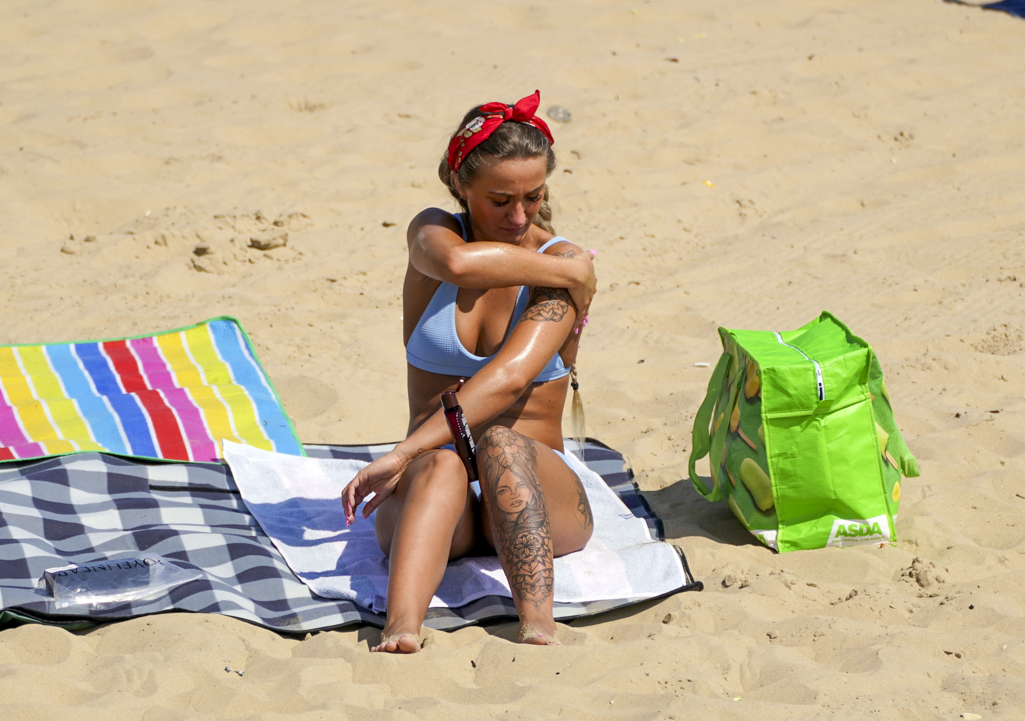 <p>A bather applies lotion as people enjoy the weather on Bournemouth beach in Dorset. Picture date: Monday July 19, 2021.</p>