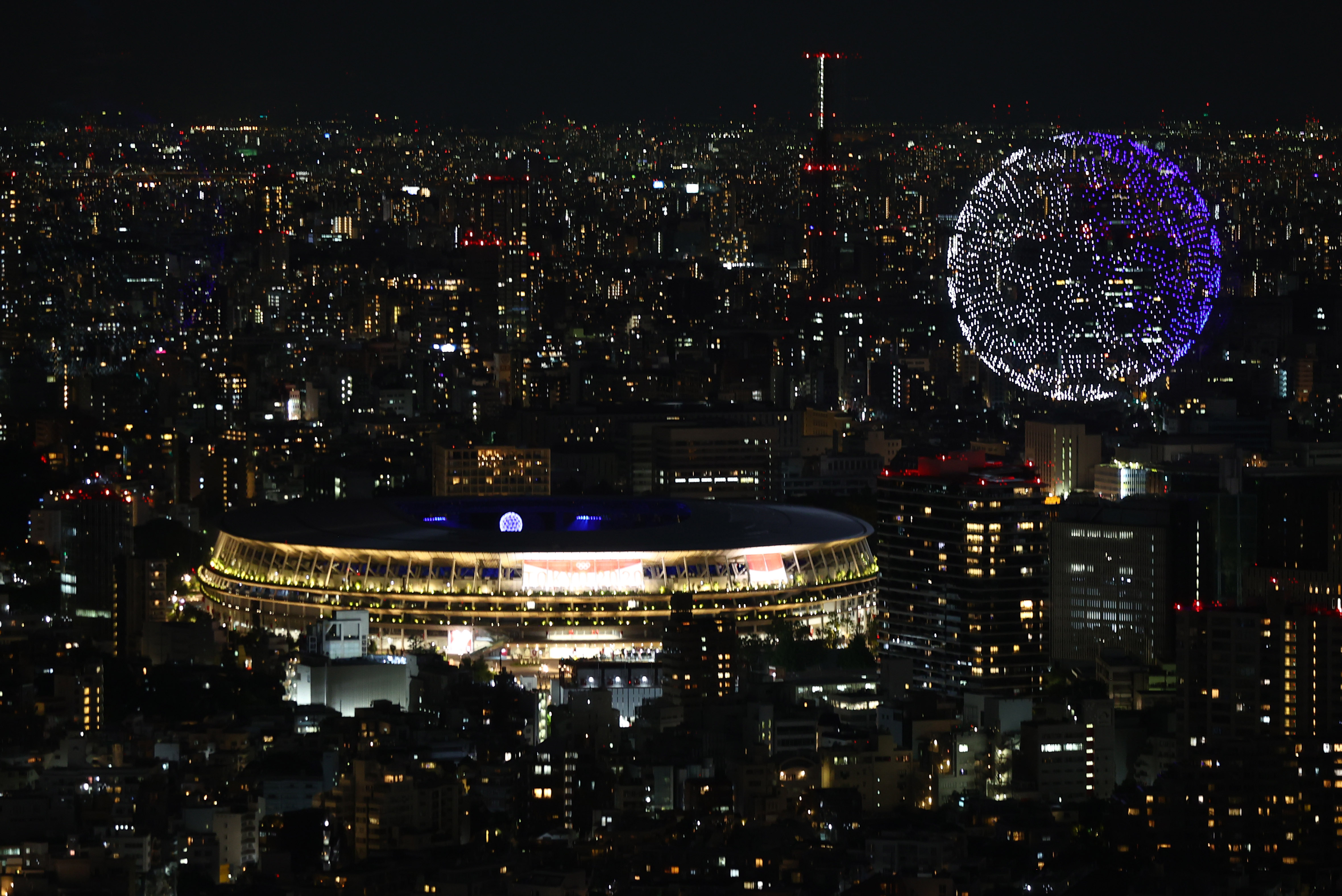 Tokyo 2020 Olympics - The Tokyo 2020 Olympics Opening Ceremony - Olympic Stadium, Tokyo, Japan - July 23, 2021. Drones form a shape of the world during the opening ceremony, seen above the Olympic Stadium REUTERS/Kim Kyung-Hoon