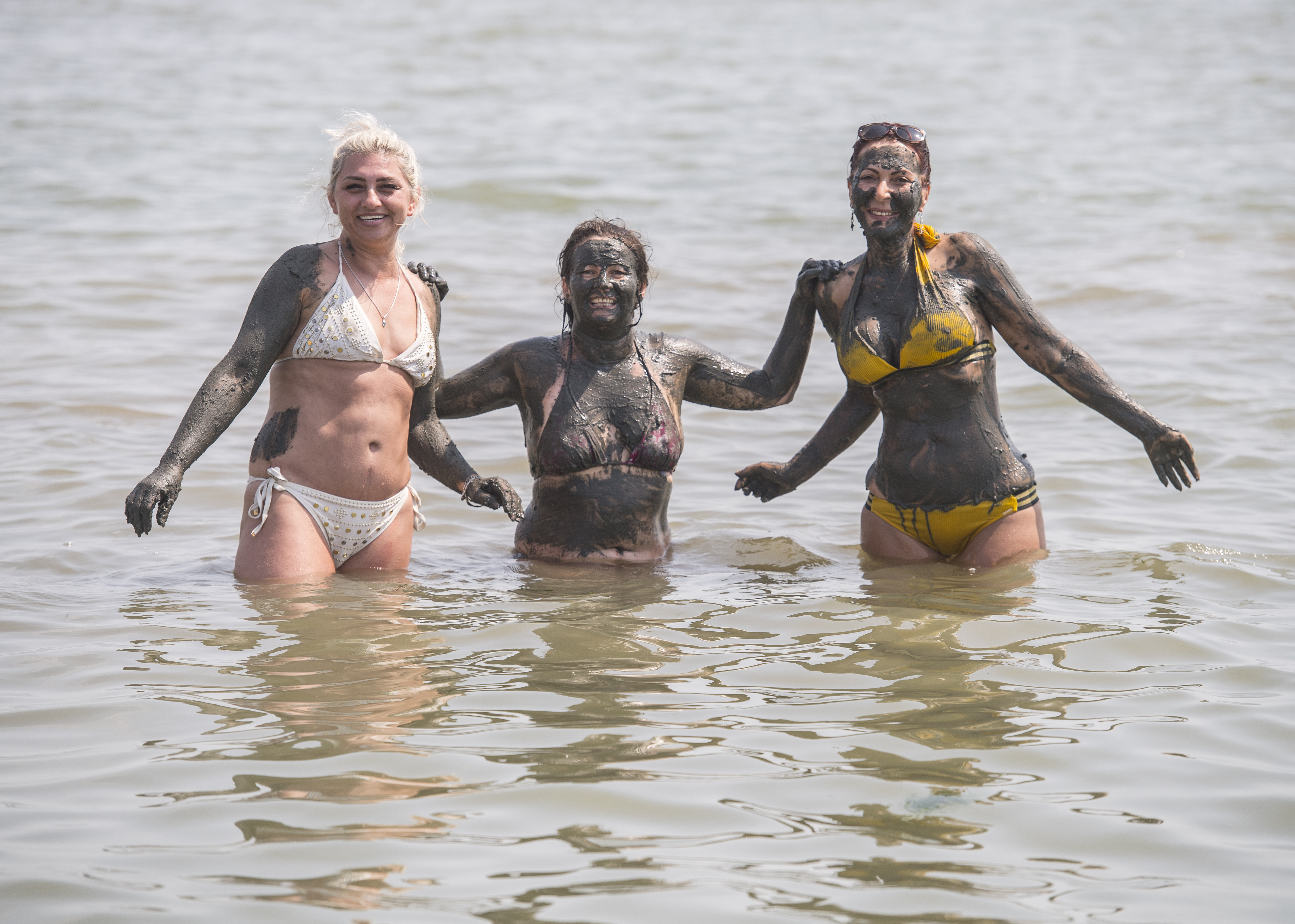 <p>Three women cover themselves in mud while enjoying the hot weather at Southend beach, Essex. Picture date: Wednesday July 21, 2021.</p>