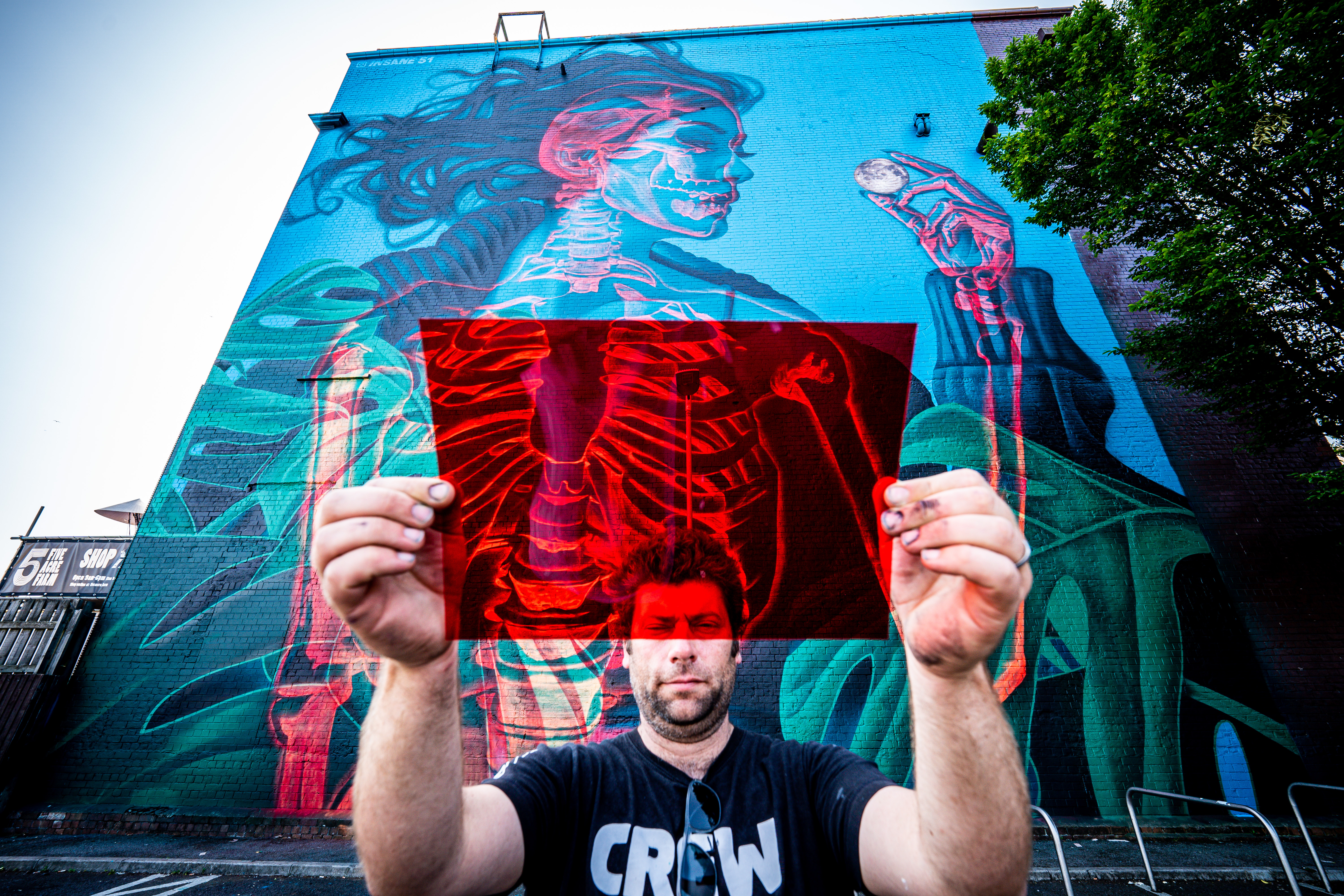 <p>Organiser of 'Upfest' Steve Hayles holds a red filter gel beside a graffiti piece by artist Insane 51, which is an interactive piece and can be viewed differently through either a blue or a red filter, like the ones in 3D glasses, revealing a woman or the skeleton within her body, on a huge wall in Bedminster, Bristol, as the 75 murals project reaches the halfway point and various graffiti pieces are sprayed onto walls and buildings across the city over the Summer. Picture date: Wednesday July 21, 2021.</p>