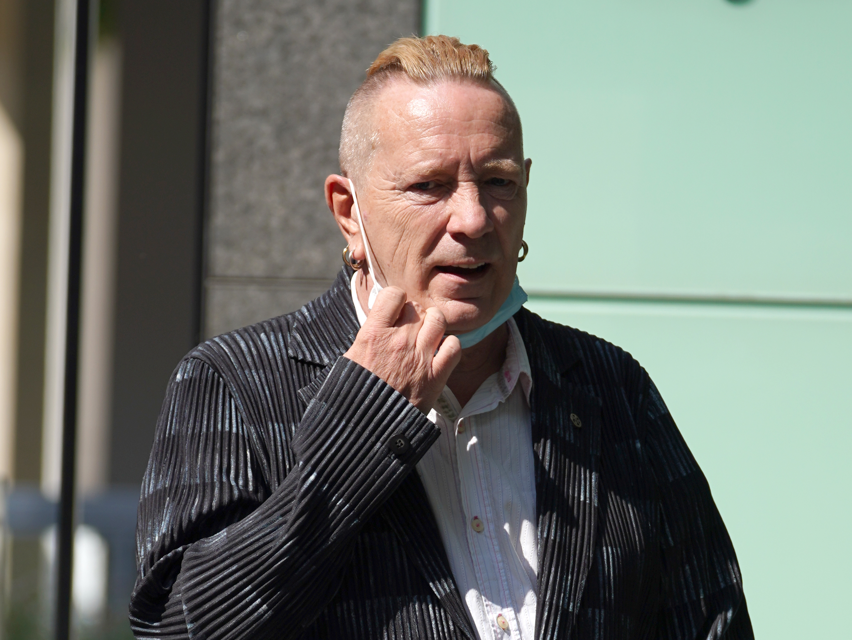 <p>John Lydon, aka Johnny Rotten, arriving at the Rolls Building at the Hight Court, London, for a hearing between two former Sex Pistols band members and the frontman over the use of their songs in a television series. Picture date: Monday July 19, 2021.</p>
