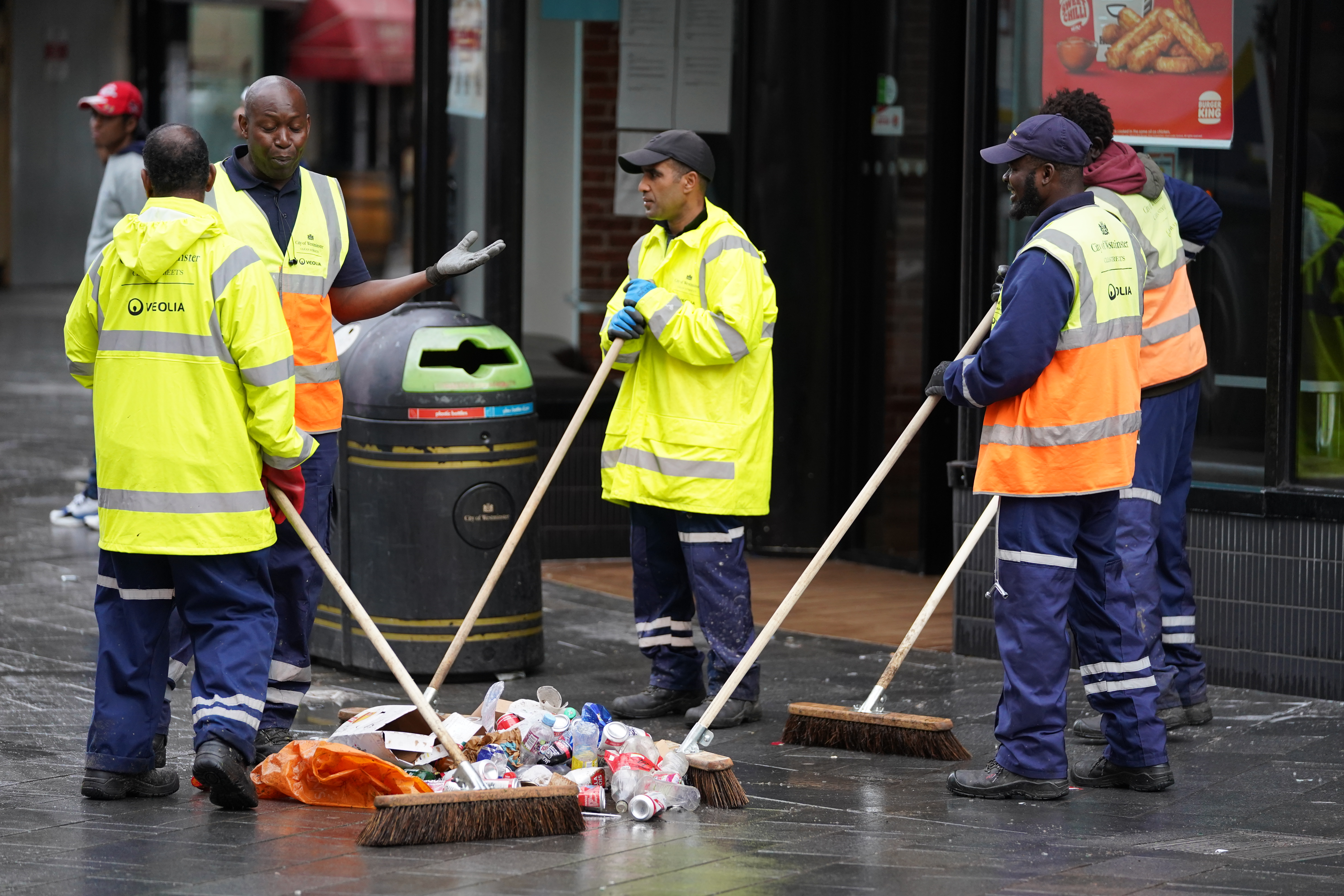 <p>Street cleaners clear debris in London's Leicester Square the morning after England were beaten in the final of the UEFA Euro 2020. Picture date: Monday July 12, 2021.</p>
