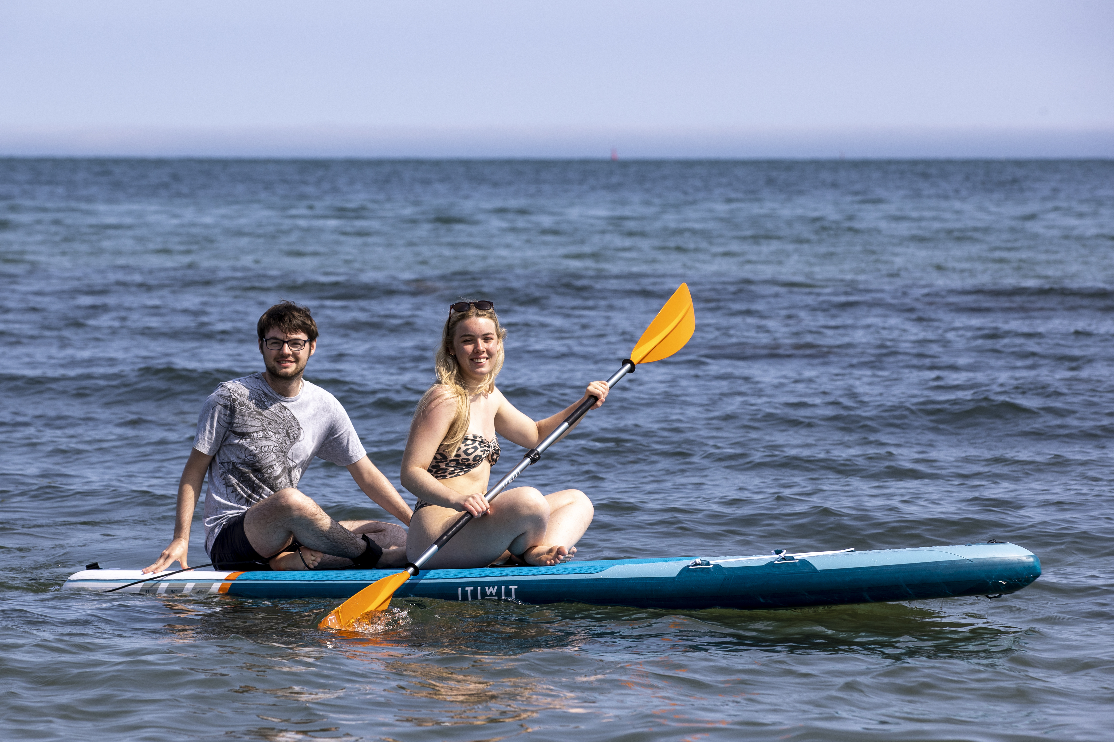 <p>Aneurin Duffin-Murray (left) and Lauren Dalzell from Belfast on a paddle board at Helen�s Bay beach in County Down, Northern Ireland. Picture date: Tuesday July 20 2021.</p>