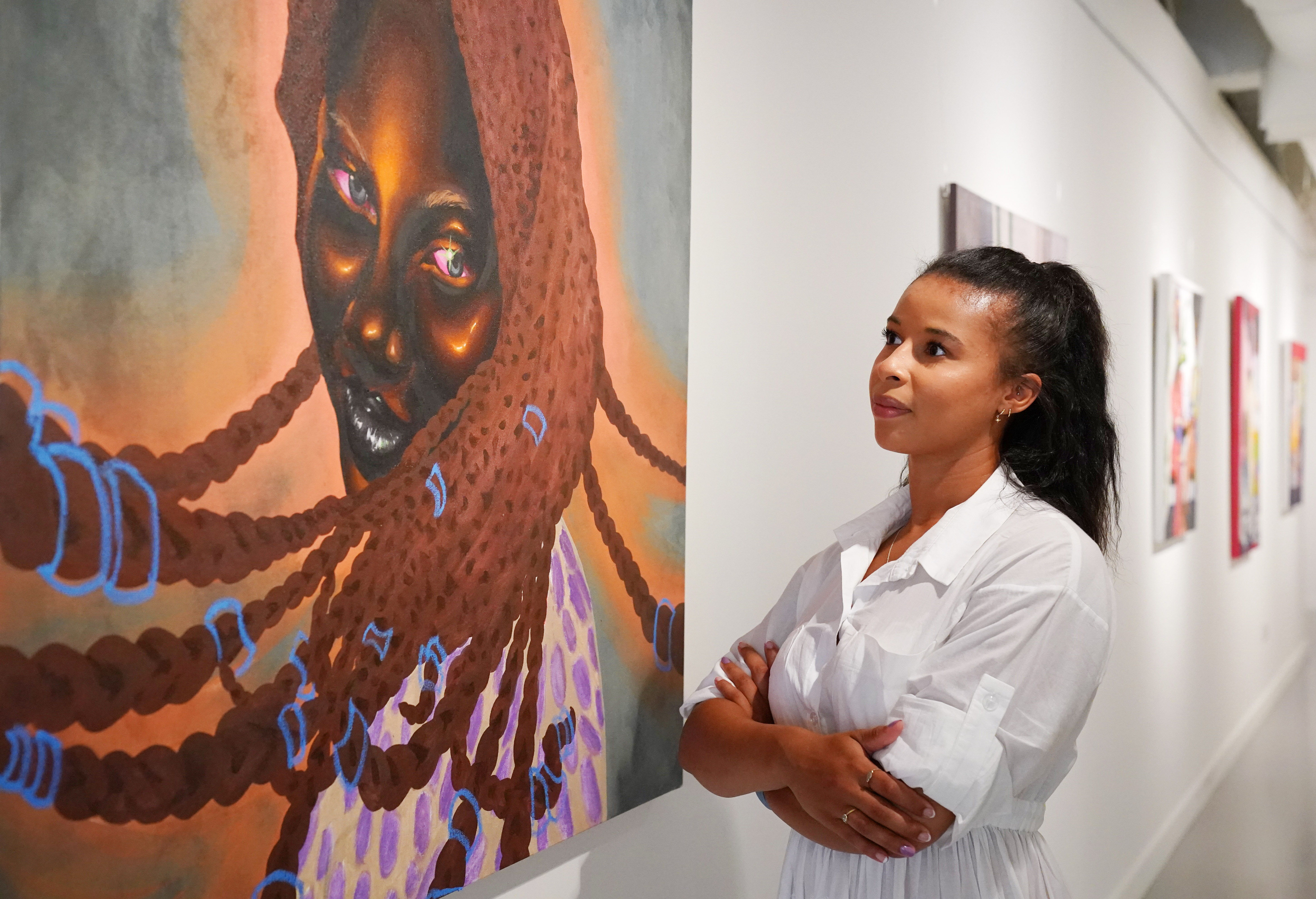 <p>A HOFA Gallery employee looks at 'Serena' by Chinaza Agbor during the preview of the Mother of Mankind exhibition, showcasing 18 black female artists, curated by Adora Mba, at the HOFA Gallery (House Of Fine Art), in Mayfair, London. Picture date: Wednesday July 21, 2021.</p>