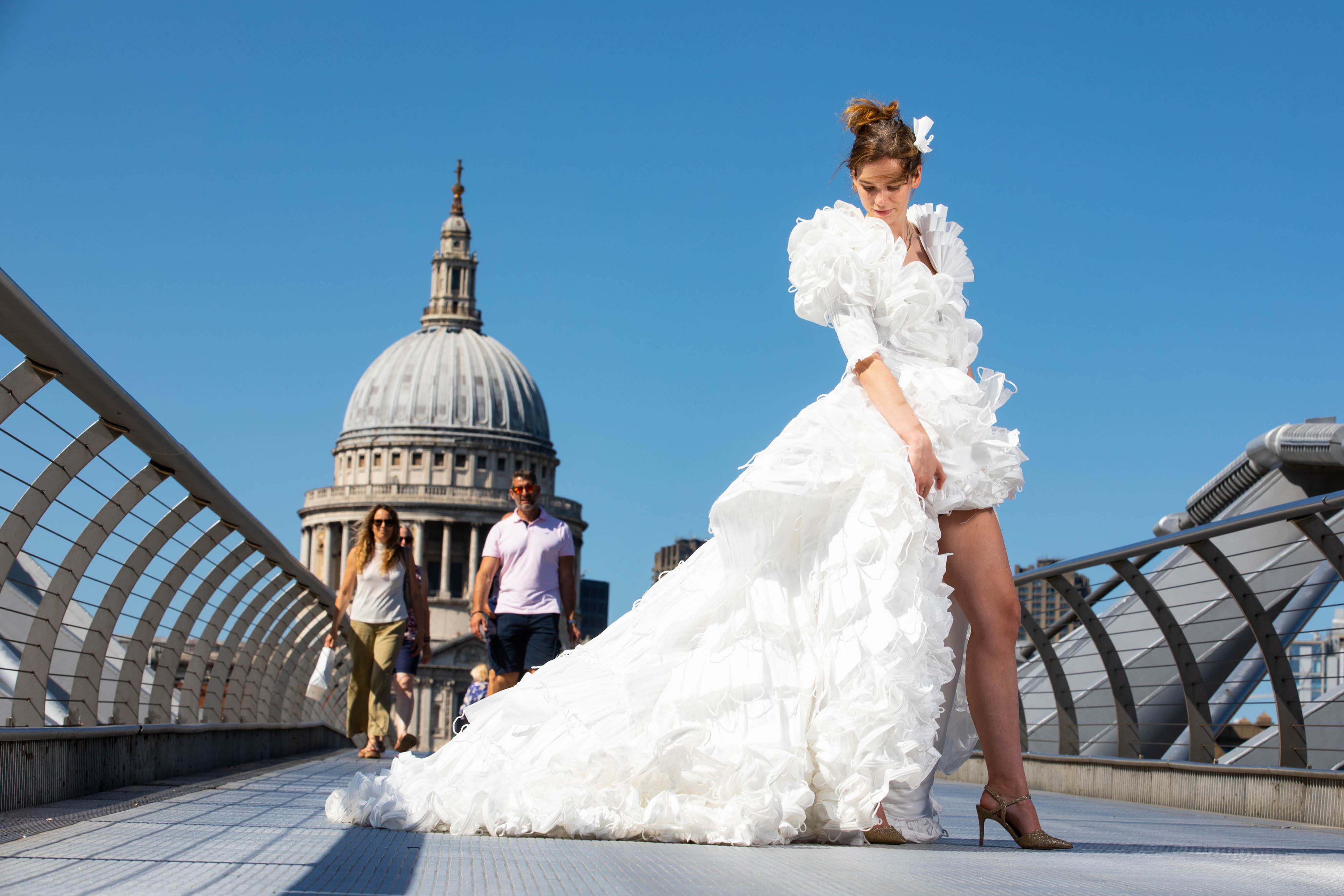 <p>EDITORIAL USE ONLY Jemima Hambro models, on the Millennium Bridge in London, a wedding dress designed by Tom Silverwood and made from over 1,500 unwanted face masks, for wedding planning website, Hitched, to celebrate all restrictions on weddings lifting in England from Monday. Issue date: Monday July 19, 2021.</p>