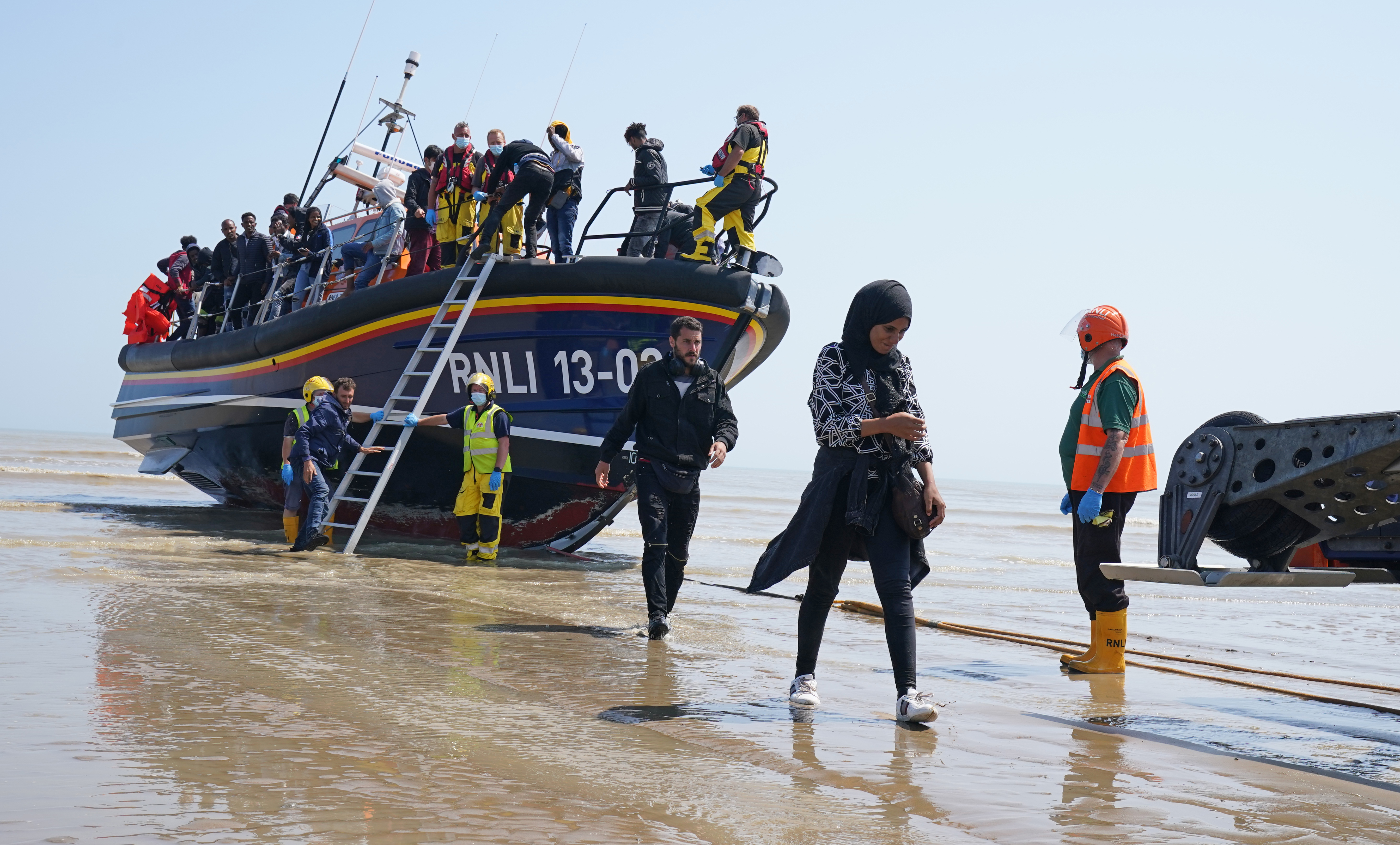 <p>A group of people thought to be migrants crossing from France come ashore from the local lifeboat at Dungeness in Kent, after being picked-up following a small boat incident in the Channel. Picture date: Tuesday July 20, 2021.</p>
