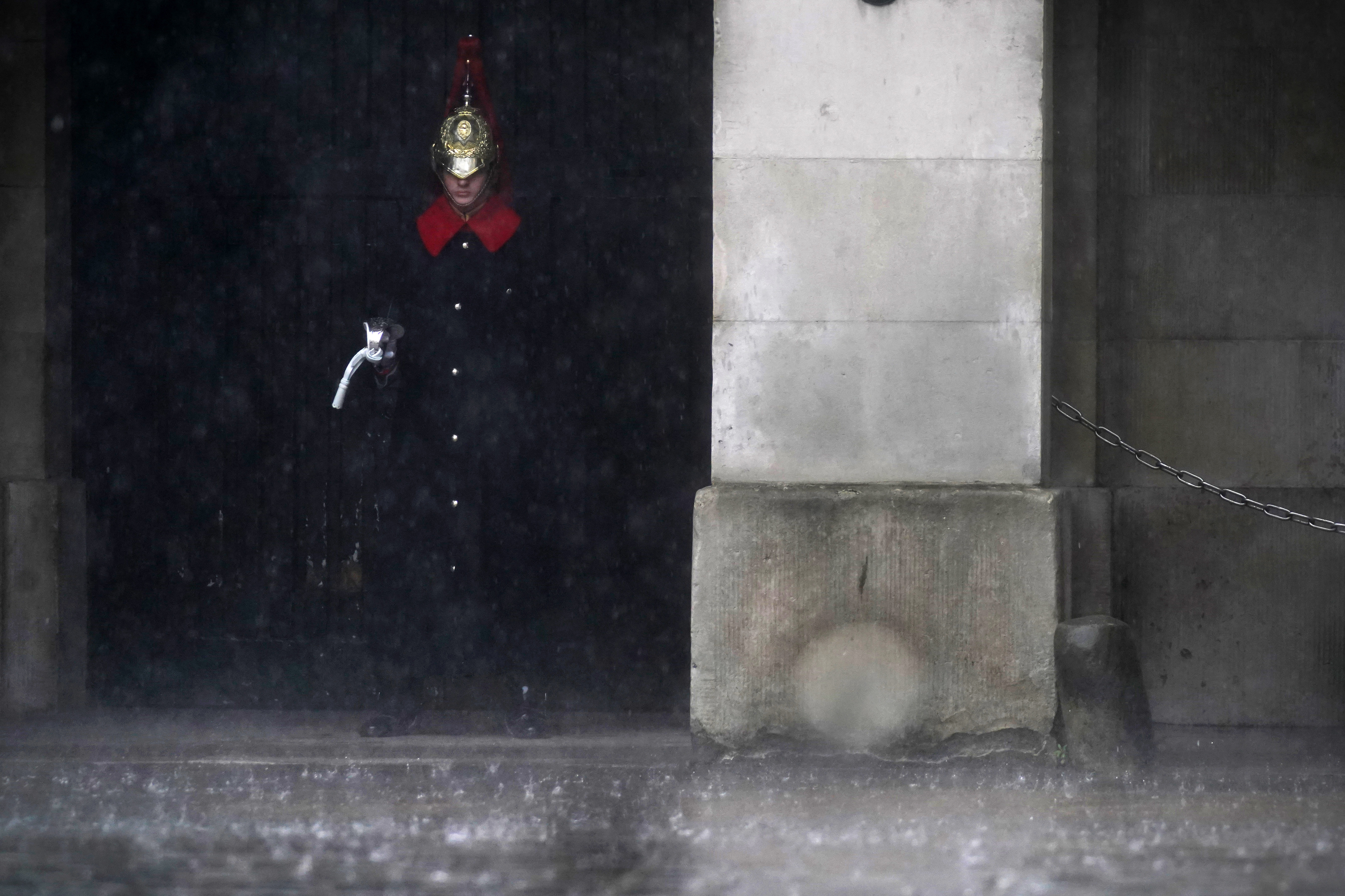 <p>A member of Household Cavalry Mounted Regiment stands in the rain at Horse Guards in Westminster as heavy rain sweeps through central London. Thunderstorms bringing lightning and torrential rain to the south are set to continue until Monday, forecasters have said. Picture date: Sunday July 25, 2021.</p>