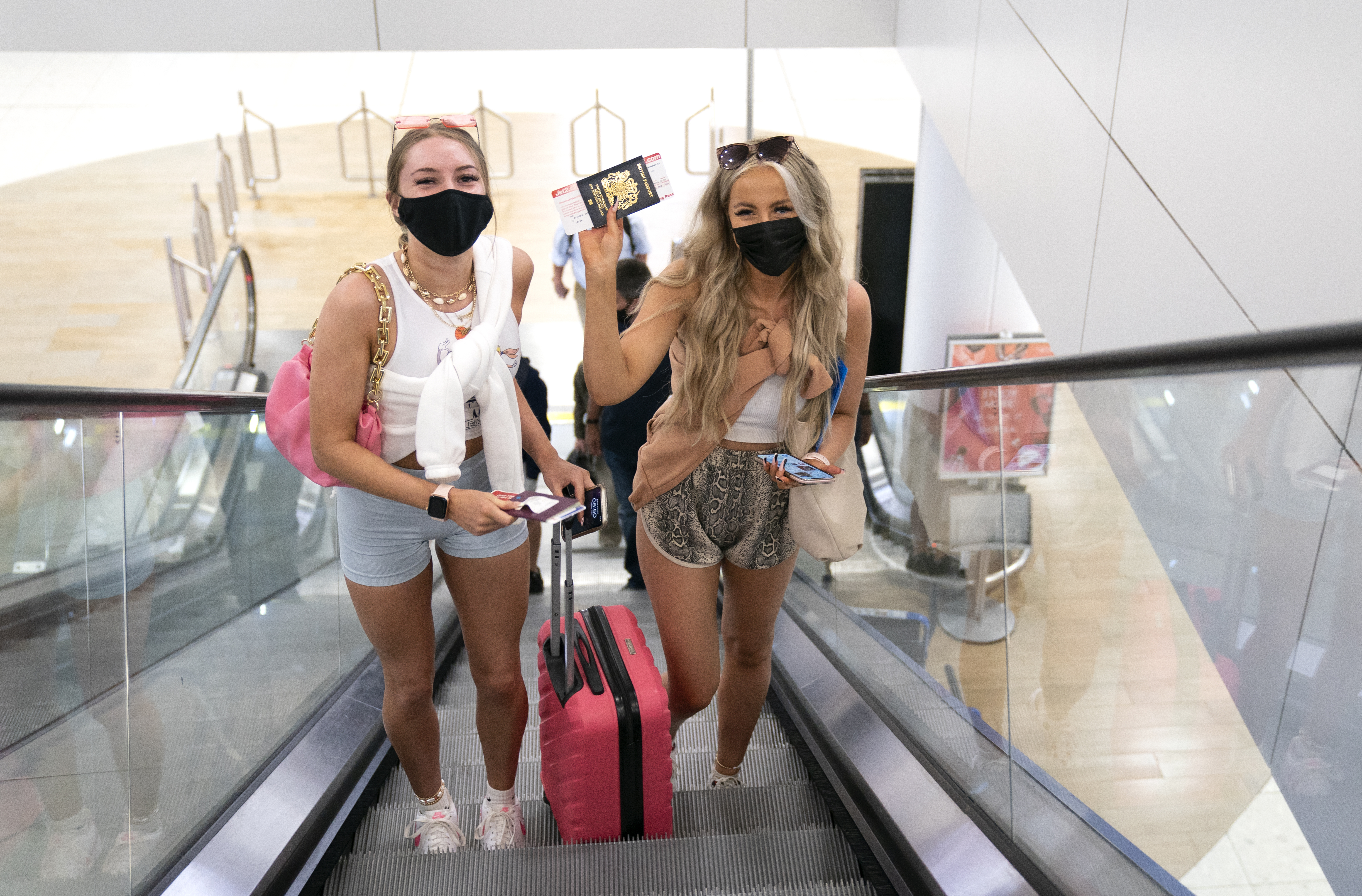 <p>Friends Poppy (left) and Shannon, both aged 20 and from Glasgow, head towards the departure gate at Glasgow Airport after checking in for their flight to Ibiza. Picture date: Monday July 19, 2021.</p>