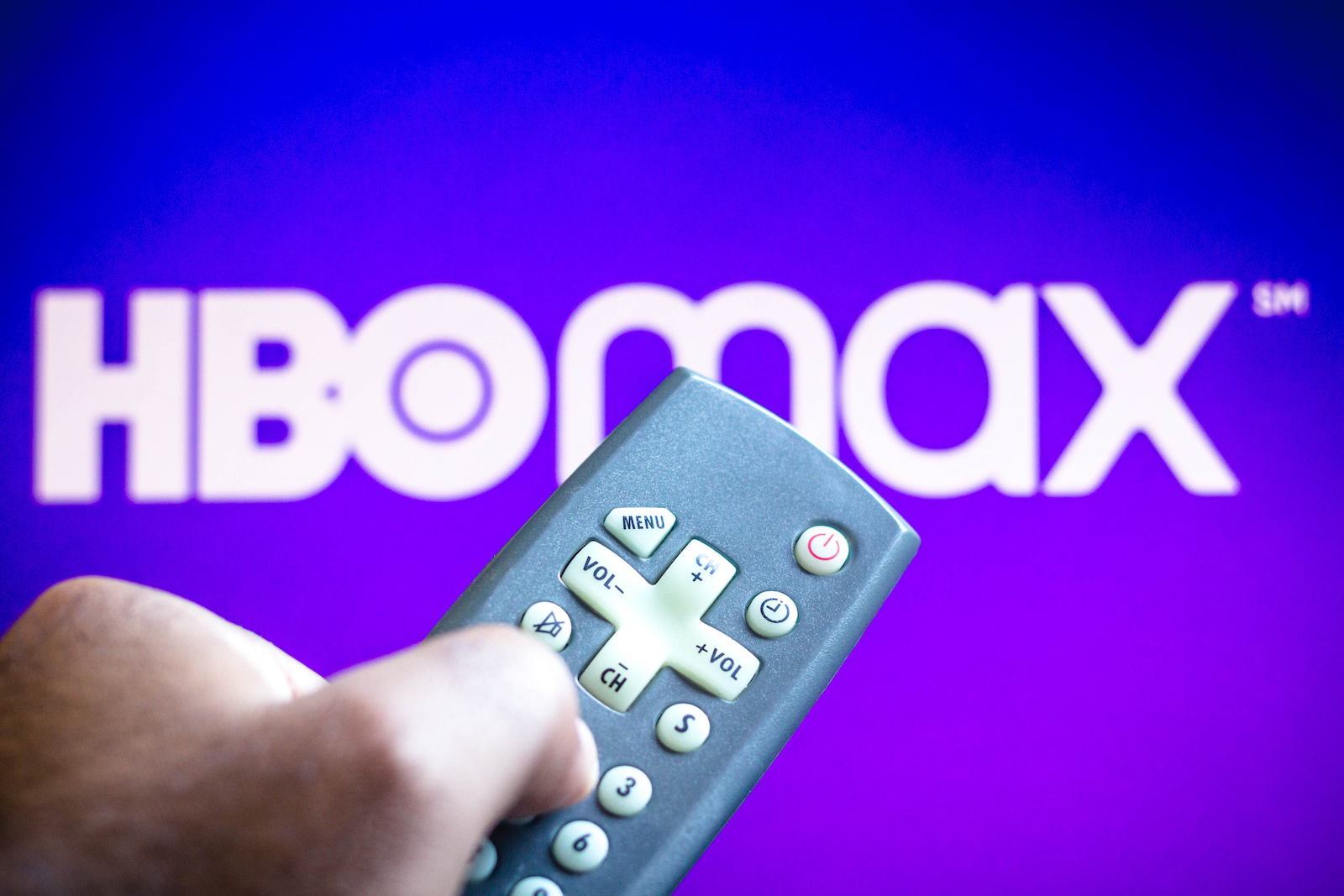 BRAZIL - 2021/06/03: In this photo illustration a close-up of a hand holding a TV remote control seen displayed in front of the HBO Max logo. (Photo Illustration by Rafael Henrique/SOPA Images/LightRocket via Getty Images)