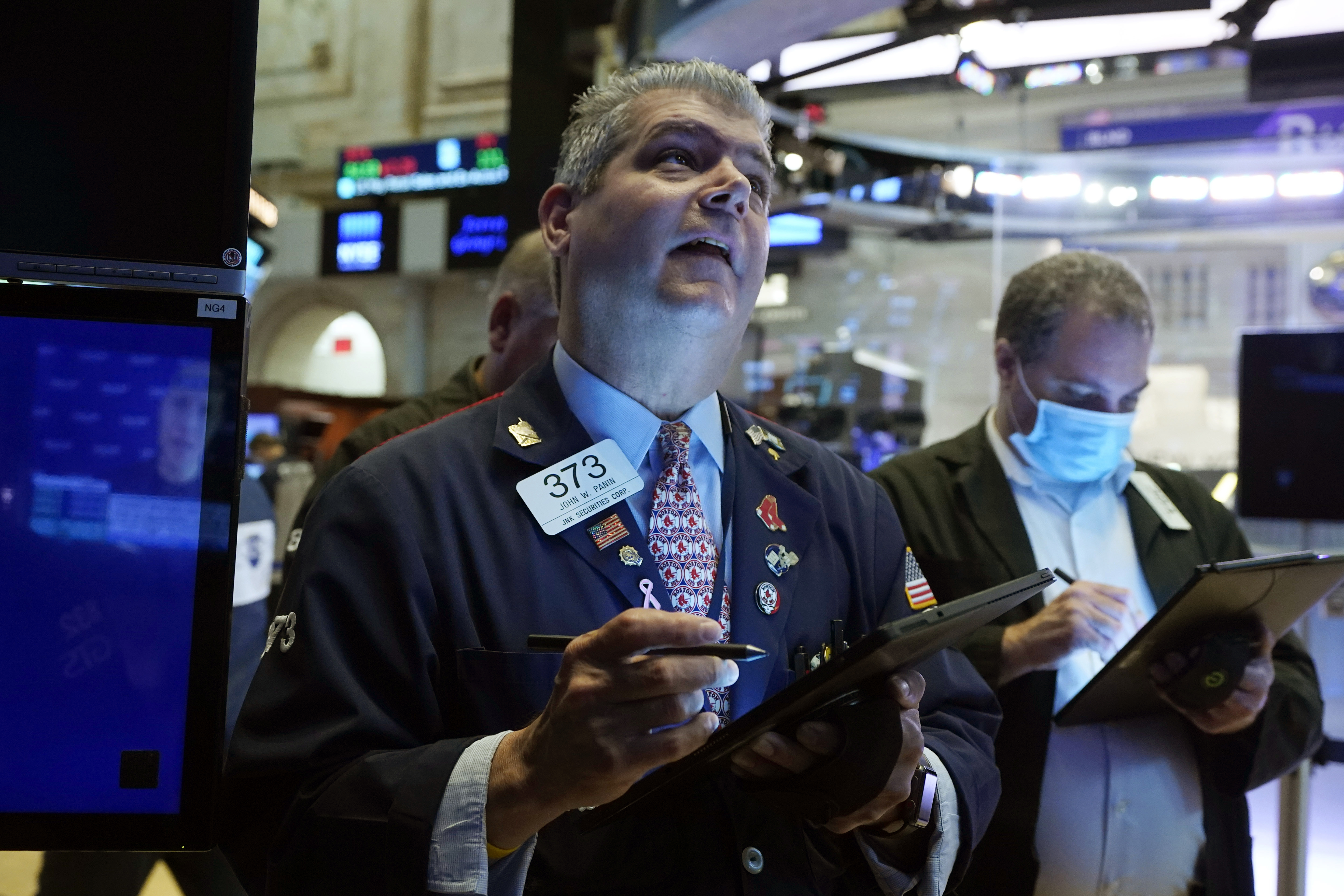 Trader John Panin, left, works on the floor of the New York Stock Exchange, Friday, July 16, 2021. Stocks edged lower Friday, dragged down by a slide from technology companies, as investors digest another round of corporate earnings. (AP Photo/Richard Drew)