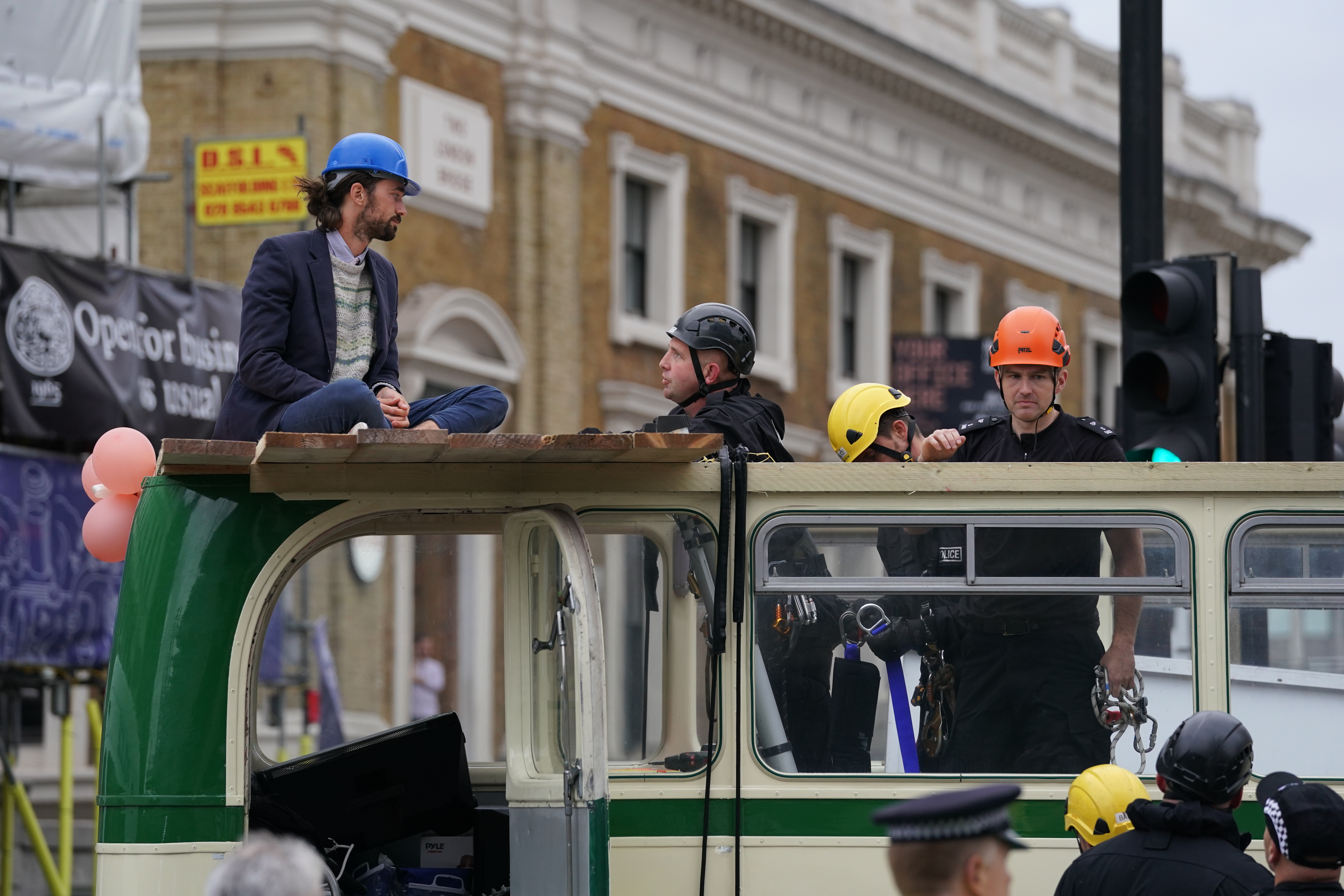 <p>Police remove a demonstrator from a bus parked on London Bridge in central London during a protest by members of Extinction Rebellion. Picture date: Tuesday August 31, 2021. (Photo by Kirsty O'Connor/PA Images via Getty Images)</p>