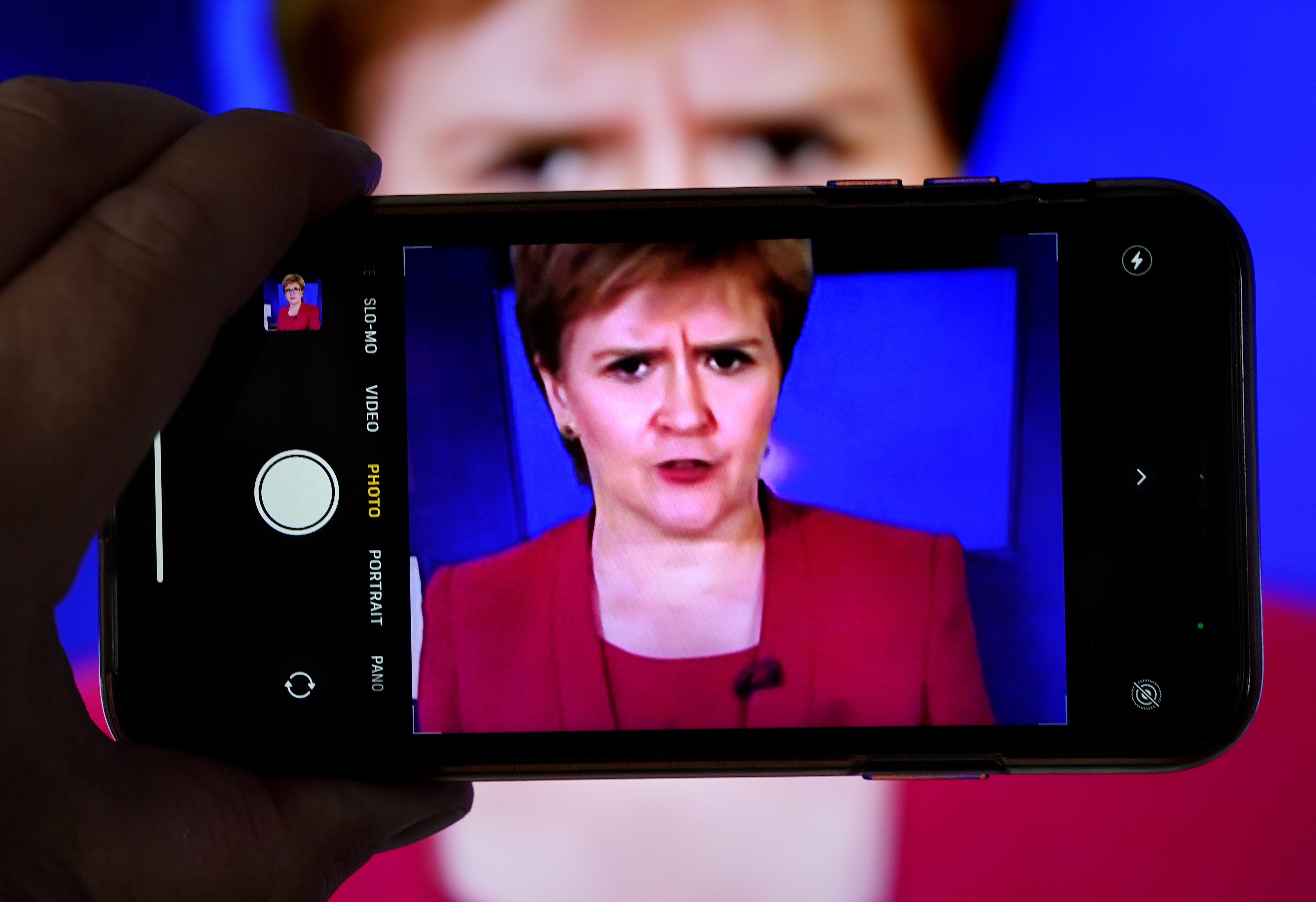 <p>A person uses their phone to film a televised broadcast of First Minister Nicola Sturgeon speaking to MSPS during a virtual sitting of the Scottish Parliament. Picture date: Tuesday August 3, 2021.</p>