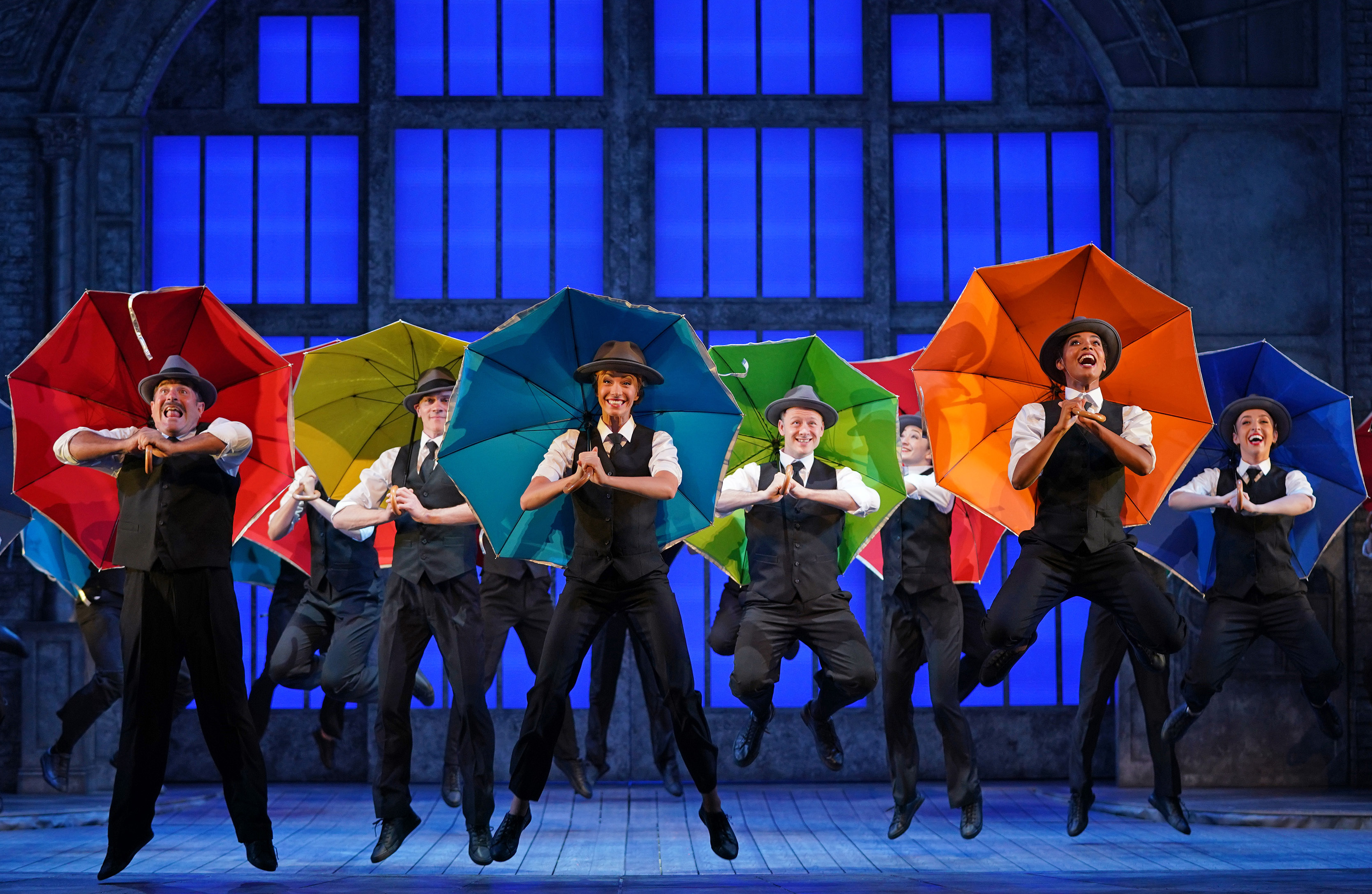 <p>Cast members, including (left to right) Adam Cooper (2nd left, yellow umbrella), Charlotte Gooch (centre, blue umbrella) and Kevin Clifton (4th right, green umbrella) at the rehearsals for Singin' in the Rain, before it re-opens later this week at Sadlers Wells Theatre in London. Picture date: Tuesday August 3, 2021.</p>