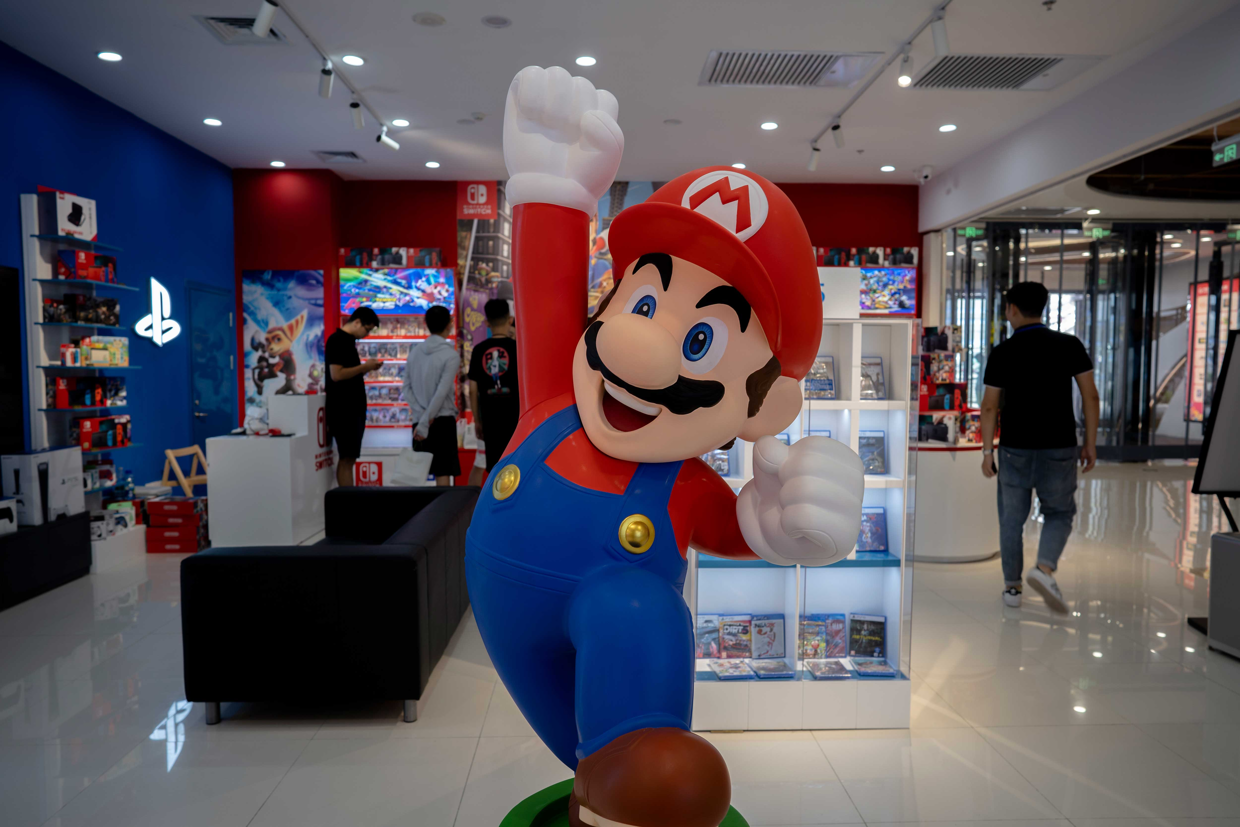 TIANJIN, CHINA - 2021/07/20: A cartoon figurine of Super Mario Bros. stands in front of a Nintendo Switch store in a shopping market.  By the end of June 2021, Nintendo's total global sales of Switch (including Switch and Switch Lite) have reached 87.43 million units, surpassing PS3 and becoming the seventh best selling host in Nintendo's history. (Photo by Zhang Peng/LightRocket via Getty Images)