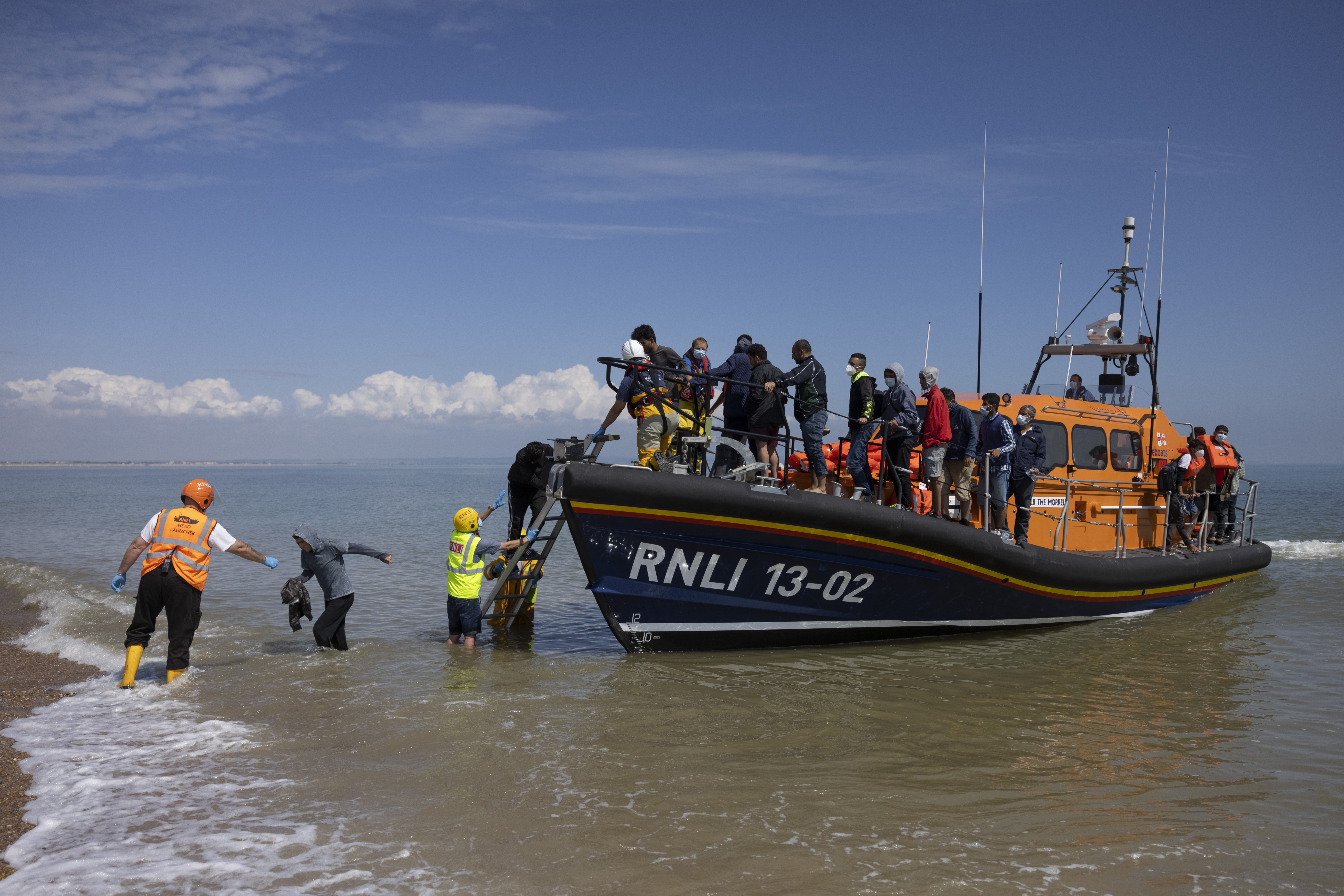 """<p>DUNGENESS, ENGLAND - AUGUST 04: A group of around 40 migrants arrive via the RNLI (Royal National Lifeboat Institution) on Dungeness beach on August 04, 2021 in Dungeness, England. UK Home Secretary Priti Patel recently said that the government would seek to criminalise irregular migration, accusing people smugglers of """"exploiting our asylum system to bring in economic migrants and people that, quite frankly, are circumventing our legal migration routes."""" (Photo by Dan Kitwood/Getty Images)</p>"""