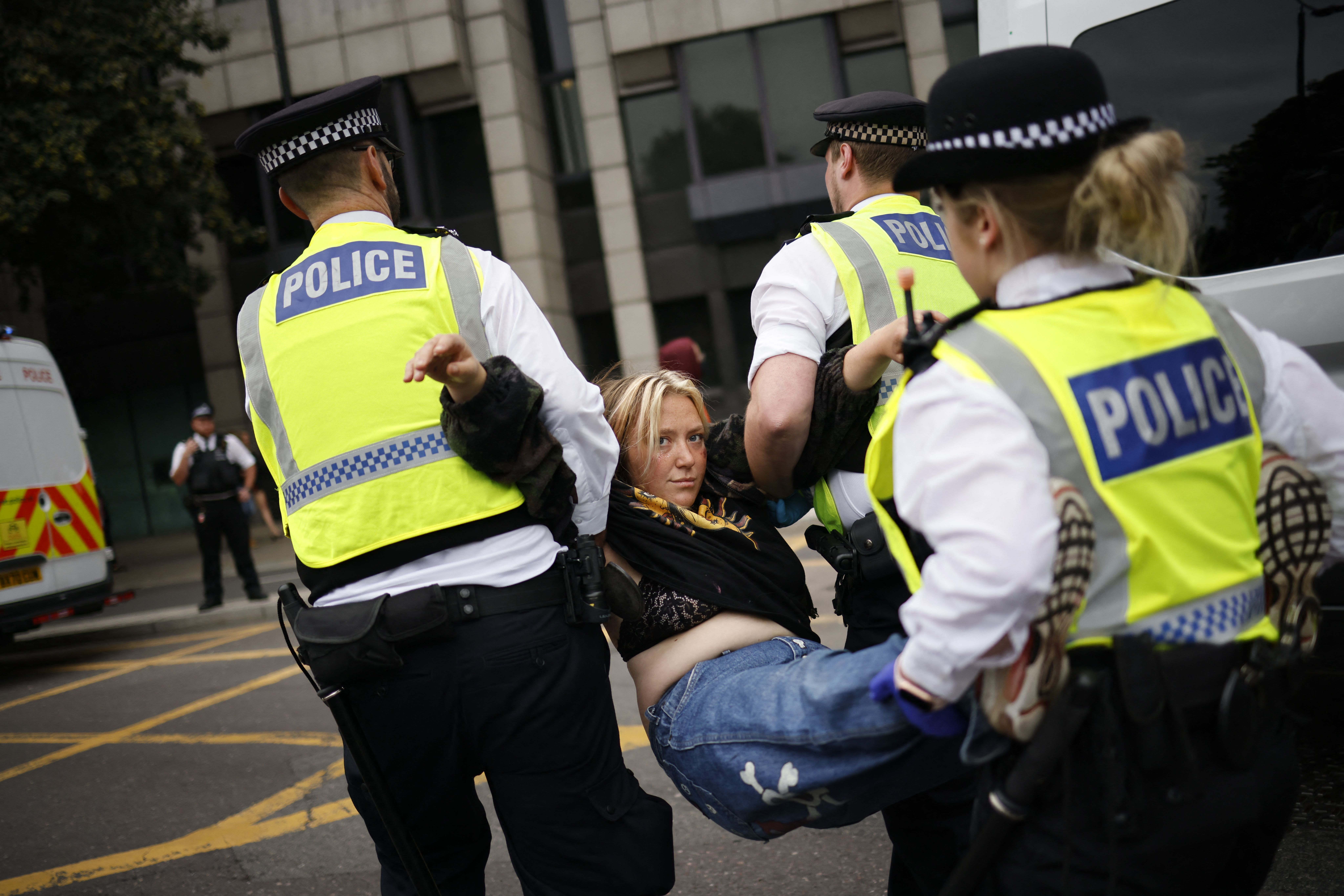 <p>Police officers escort away a climate activists from the Extinction Rebellion group blocking the road leading to Tower Bridge in central London on August 30, 2021 during the group's 'Impossible Rebellion' series of actions. - Climate change demonstrators from environmental activist group Extinction Rebellion continued with their latest round of protests in central London, promising two weeks of disruption. (Photo by Tolga Akmen / AFP) (Photo by TOLGA AKMEN/AFP via Getty Images)</p>