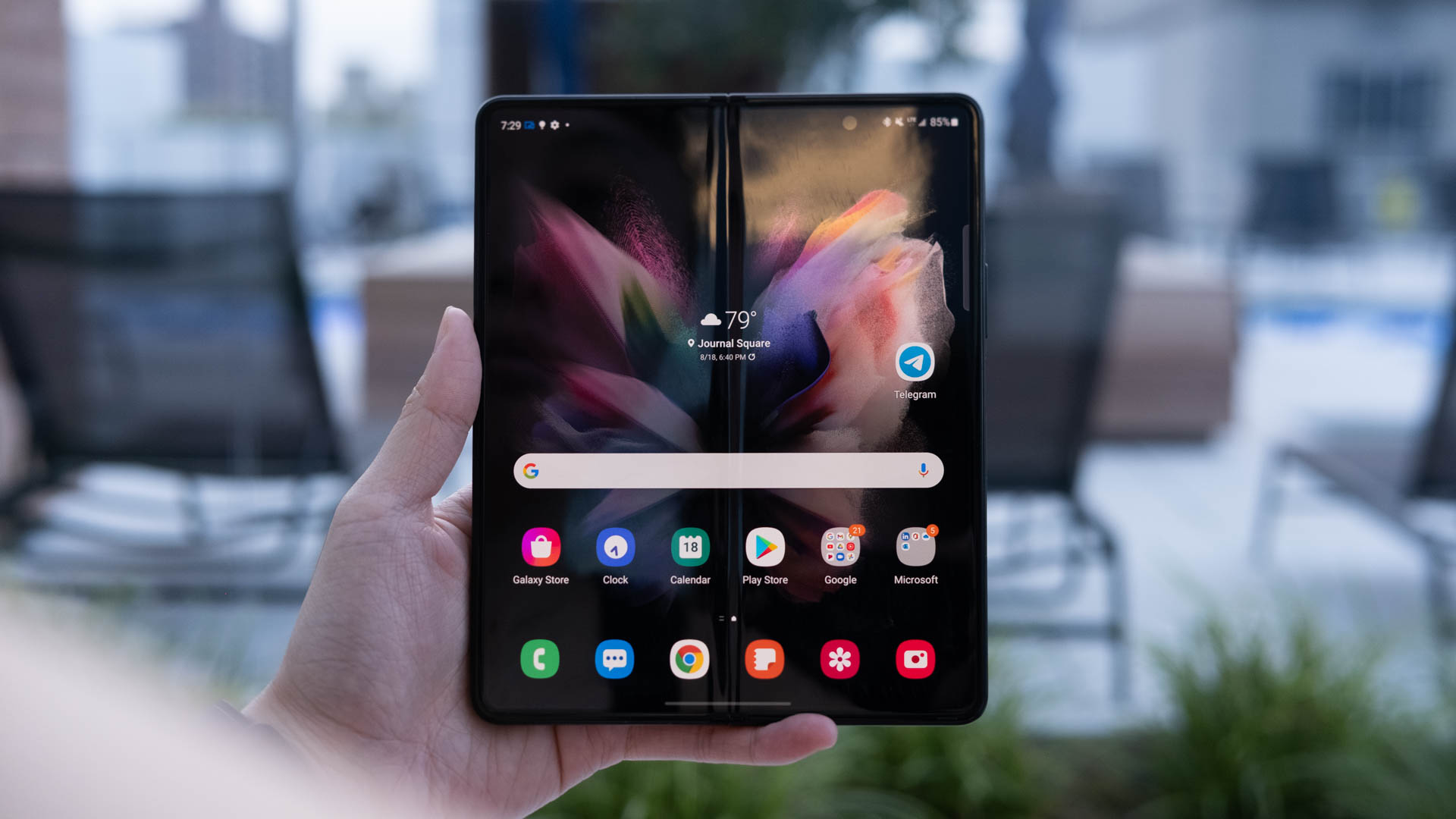 A hand holding up the Samsung Galaxy Z Fold 3 with its screen open and facing the camera. A crease runs down the middle of the home page.