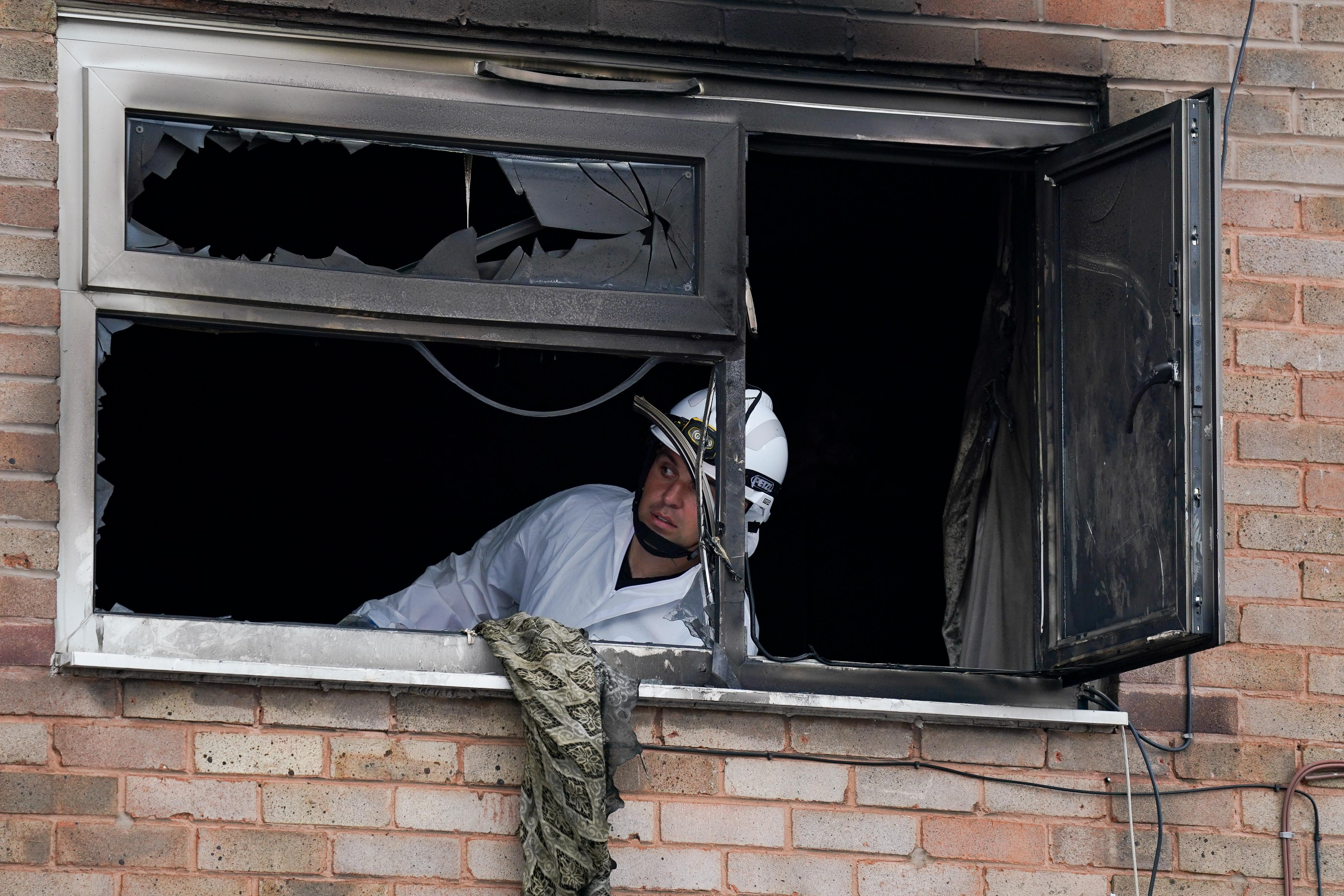 <p>Officers at a property on Tame Road in Tipton, West Midlands, where a house fire Tuesday evening has caused the death of a man and left a woman in hospital with smoke inhalation. An 18-year-old woman has been arrested on suspicion of arson. Picture date: Wednesday August 4, 2021.</p>