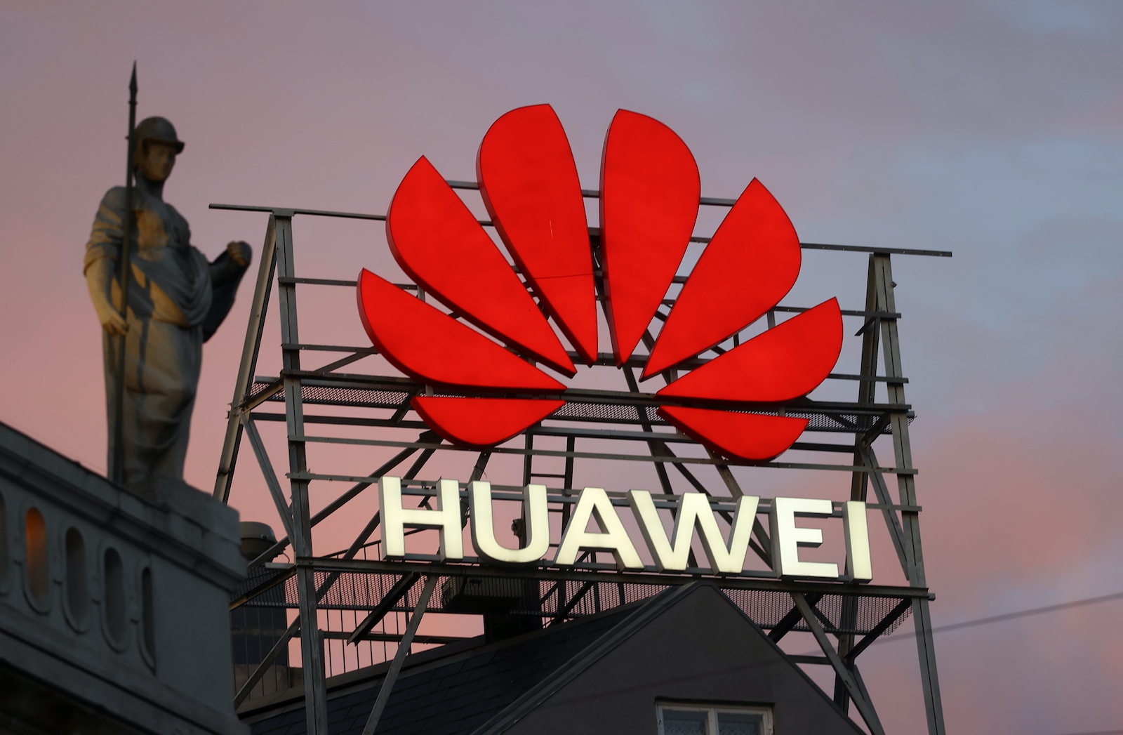 The logo of the Chinese telecommunications giant Huawei Technologies is pictured next to a statue on top of a building in Copenhagen, Denmark, June 23, 2021. REUTERS/Wolfgang Rattay - RC2J6O9U7F43