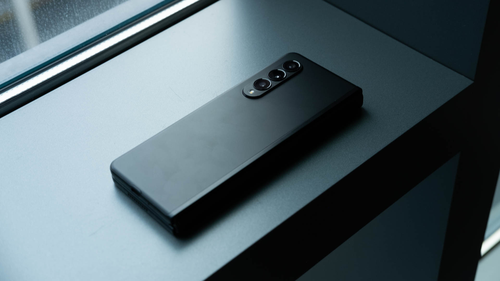 A closed Samsung Galaxy Z Fold 3 sitting on a window ledge with its triple cameras facing up.
