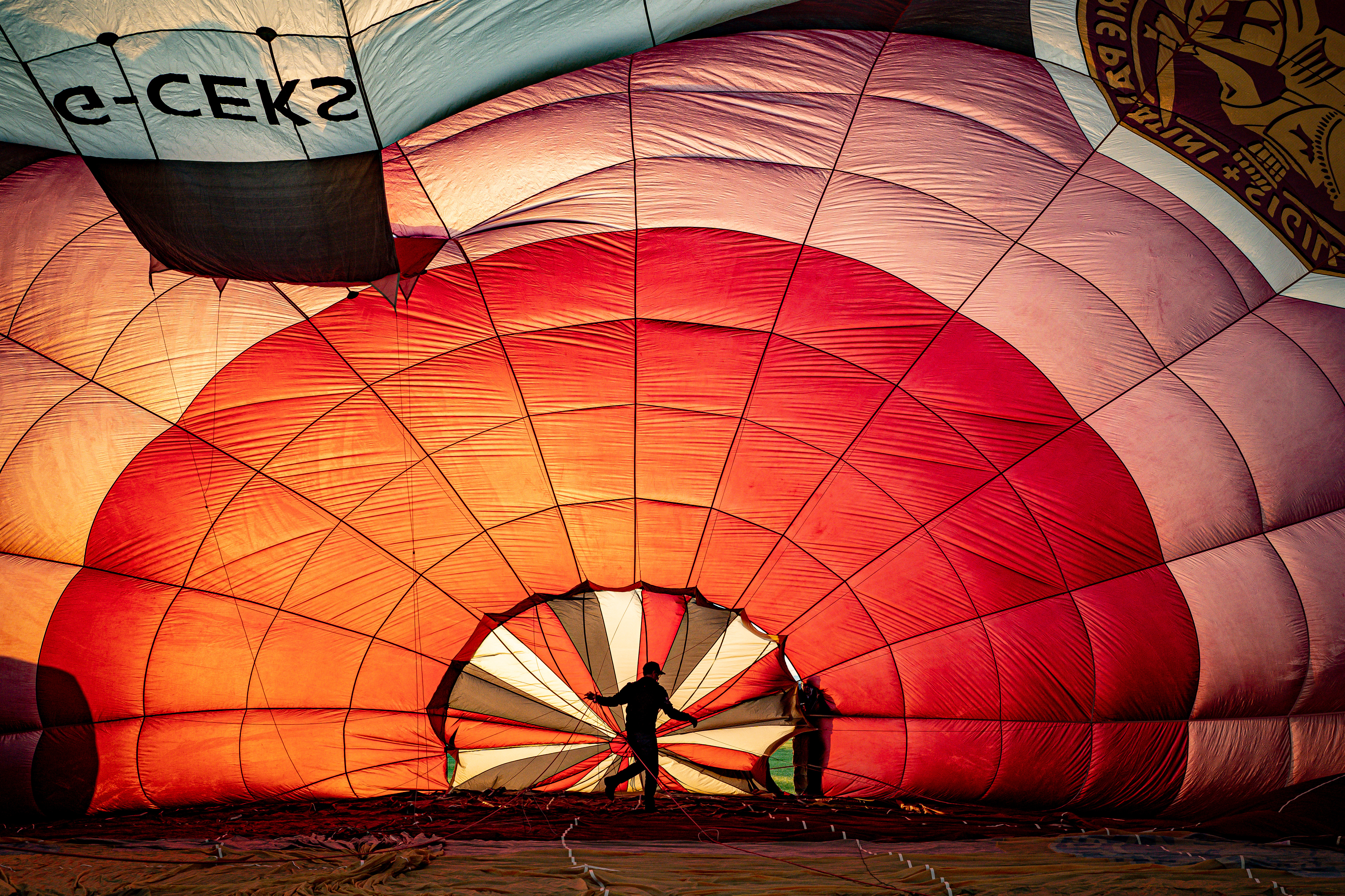 <p>Balloon pilots check the rigging inside a balloon canopy as they prepare for the first mass ascent from Filton, Bristol, during 'Fiesta Fortnight' that will see hundreds of balloons above the skies of Bristol over two weeks, culminating in the Bristol International Balloon Fiesta at Ashton Court Estate. Picture date: Wednesday August 4, 2021.</p>