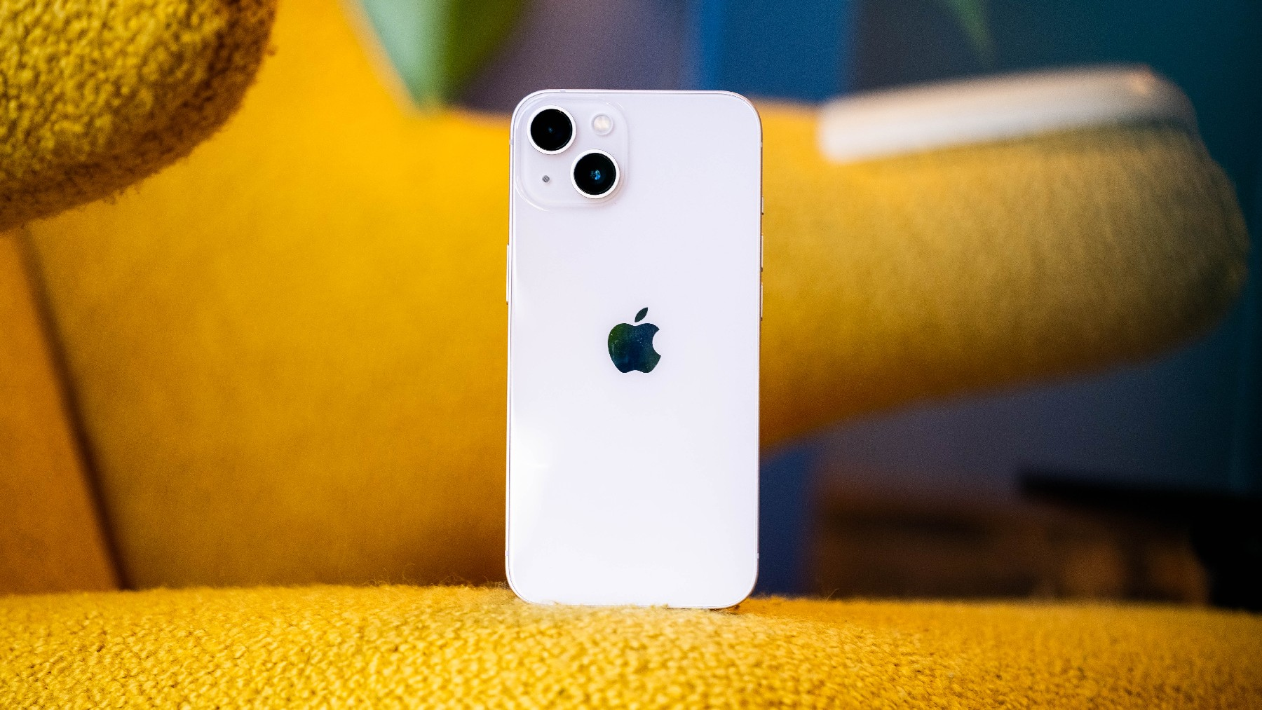 A pink iPhone 13 on a mustard-colored couch with its rear facing the camera.