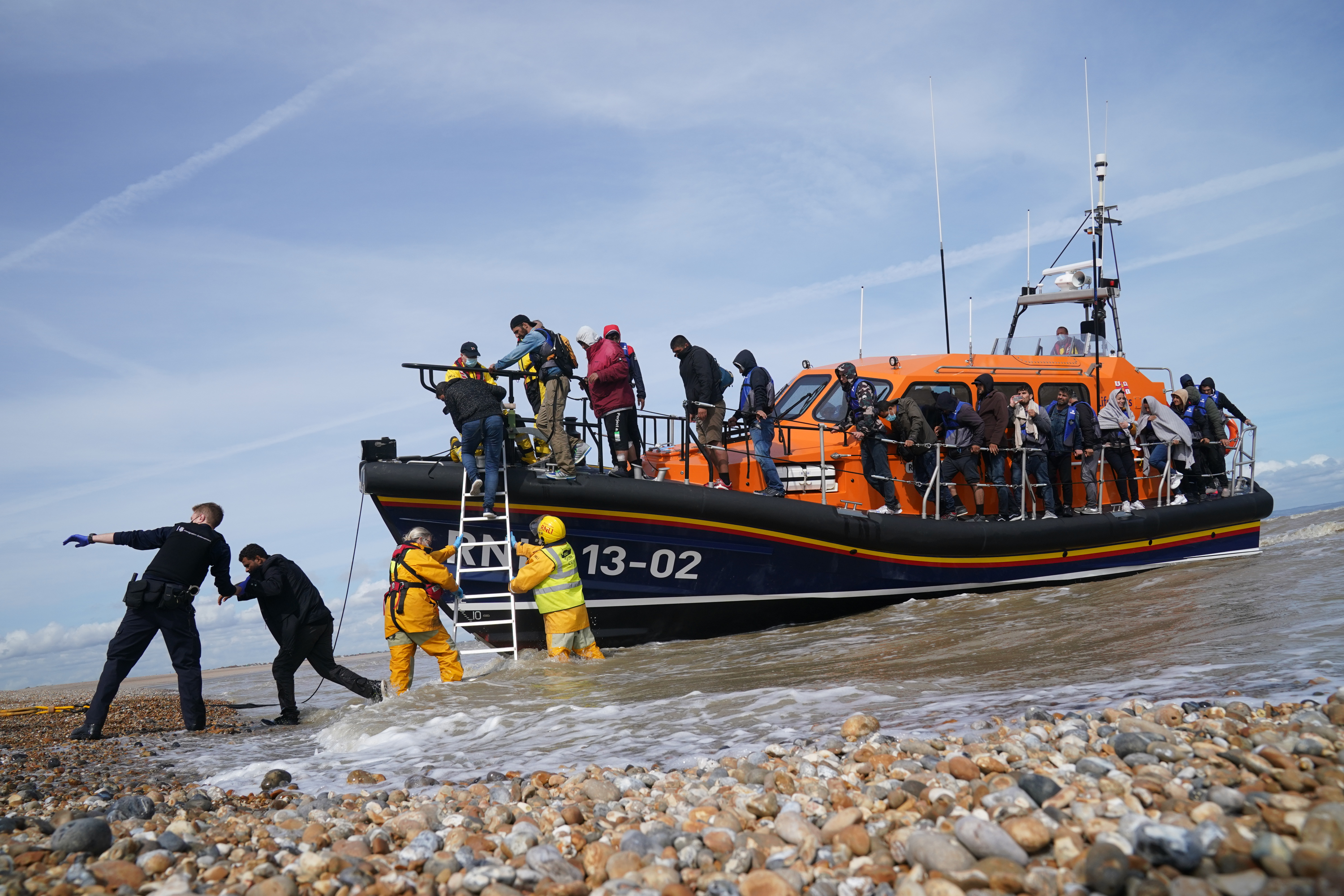 <p>Immigration Enforcement officers and members of the RNLI assist a group of people thought to be migrants from an RNLI lifeboat after they were brought into Dungeness, Kent, by an RNLI lifeboat following a small boat incident in the Channel. Picture date: Monday September 13, 2021.</p>
