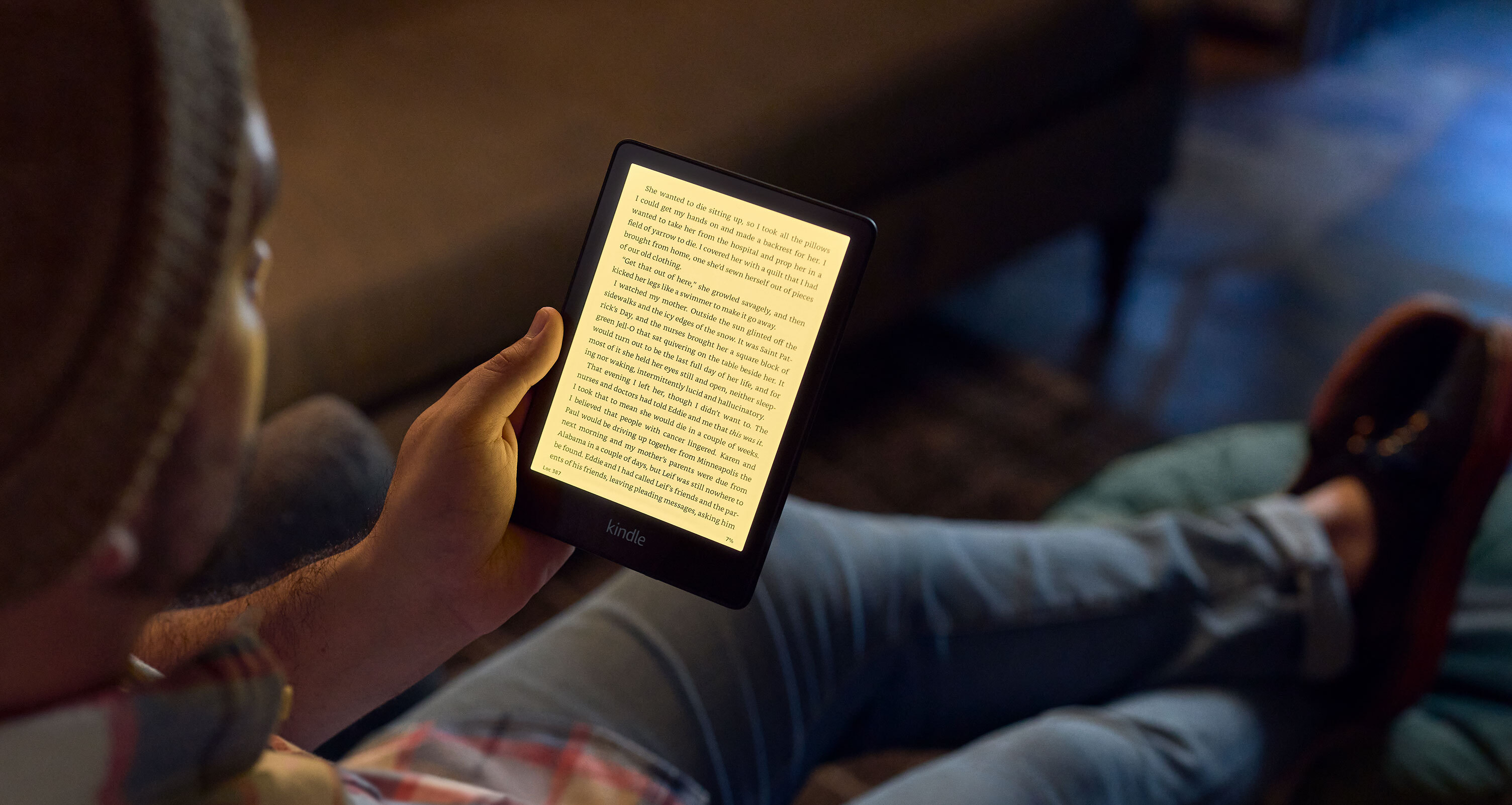 A seated person reading text on a fifth-generation Kindle Paperwhite.