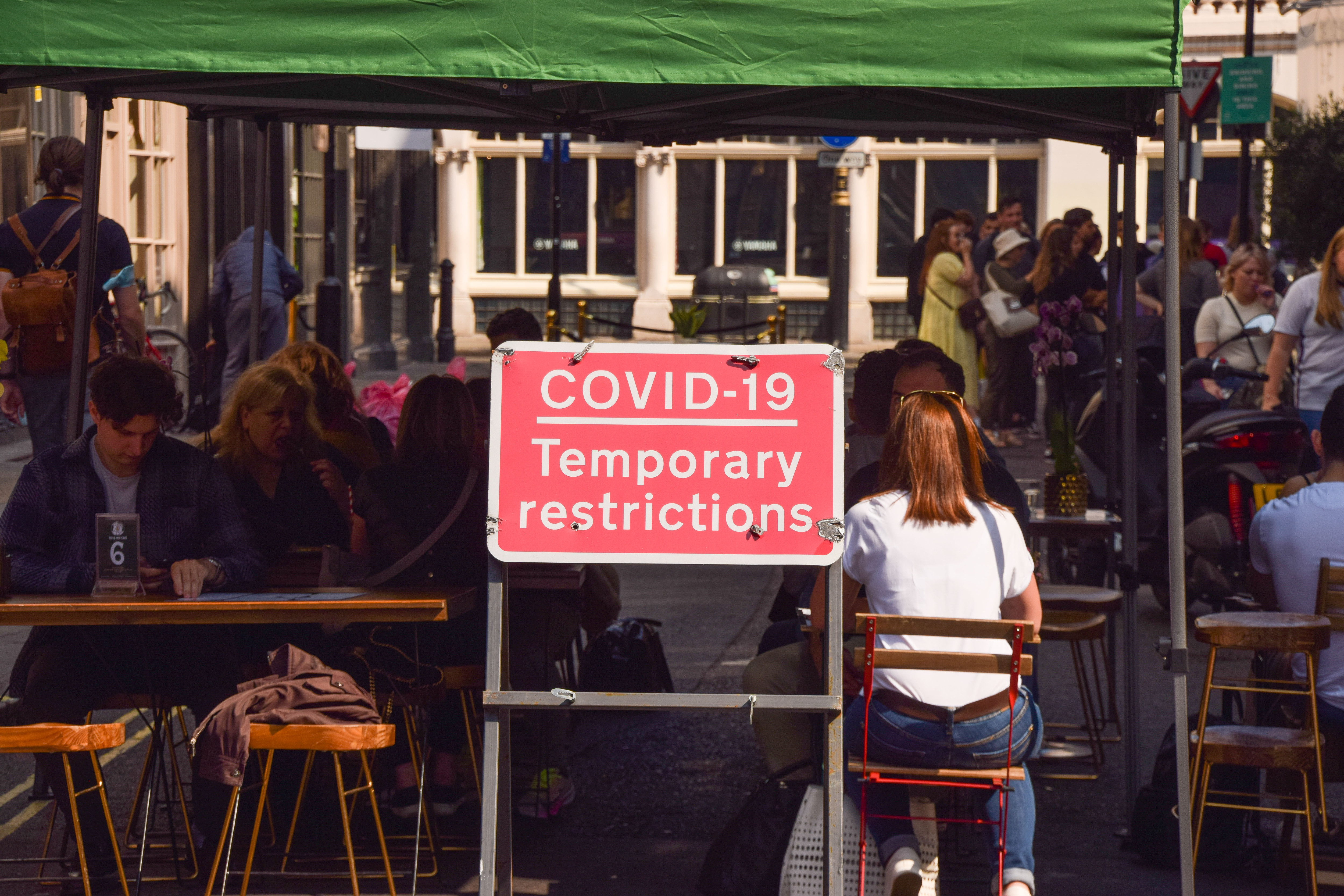 <p>LONDON, UNITED KINGDOM - 2021/09/05: A 'COVID-19 Temporary Restrictions' sign is seen outside busy restaurants and cafes in D'Arblay Street, as temporary al fresco, street seating continues in Soho. Several streets in Central London have been blocked for traffic at certain times of the day and at weekends to allow street seating at bars, cafes and restaurants during the coronavirus pandemic. (Photo by Vuk Valcic/SOPA Images/LightRocket via Getty Images)</p>