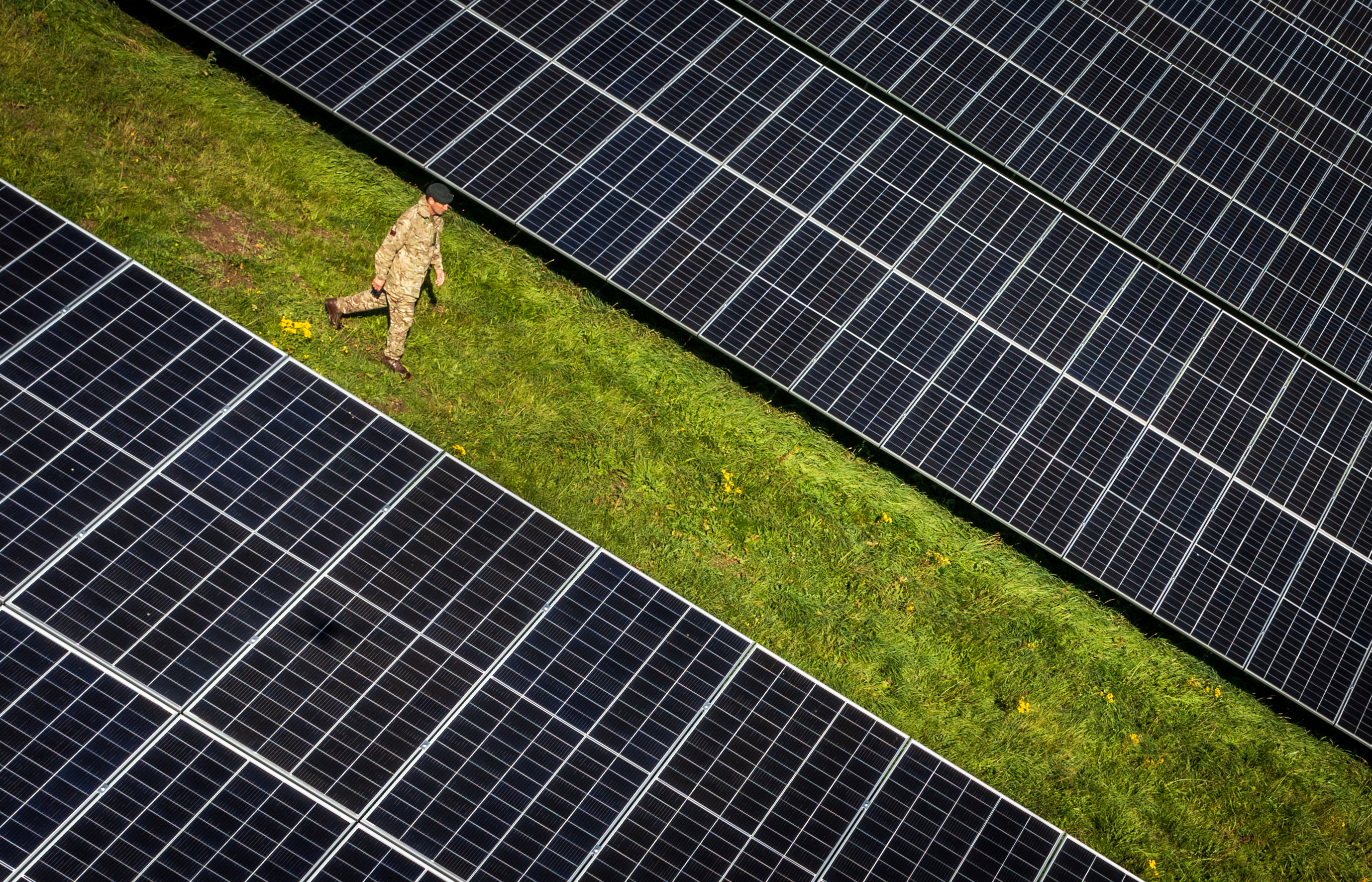 <p>Major David Owen walks through a field of solar panels at the opening of the British Army's first ever solar farm, part of Project PROMETHEUS at the Defence School of Transport (DST), Normandy Barracks, in Leconfield, in the East Riding of Yorkshire. Picture date: Wednesday September 29, 2021.</p>