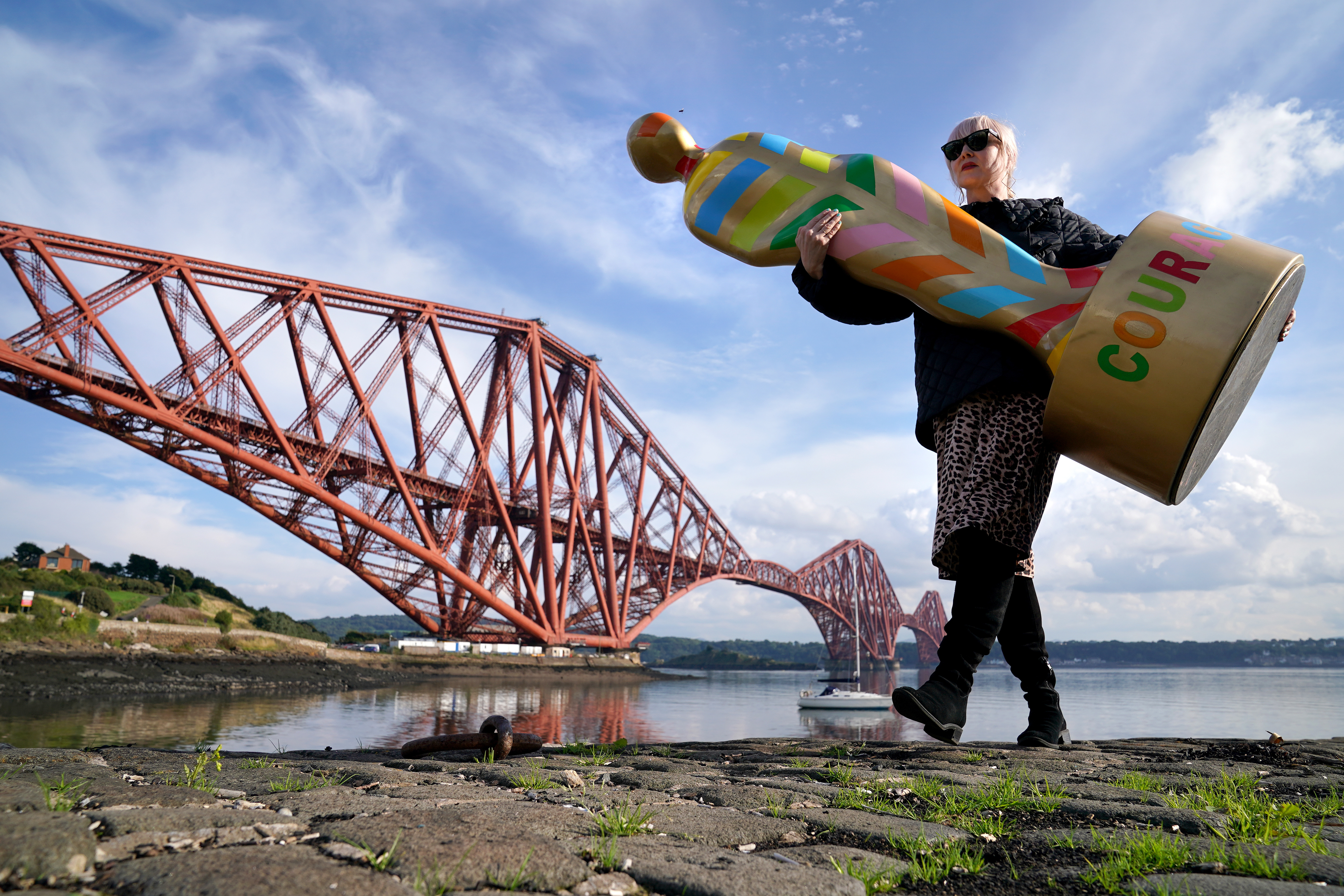 <p>Fiona McGarva holds one of the sculptures from the art installation Gratitude at The Forth Bridge at North Queensferry, ahead of going on display just outside of Edinburgh at Newhailes House and Gardens from Friday 17th September. The public art installation pays tribute to NHS staff and all key workers for their ongoing courage and dedication during the Covid-19 pandemic. Picture date: Wednesday September 15, 2021.</p>