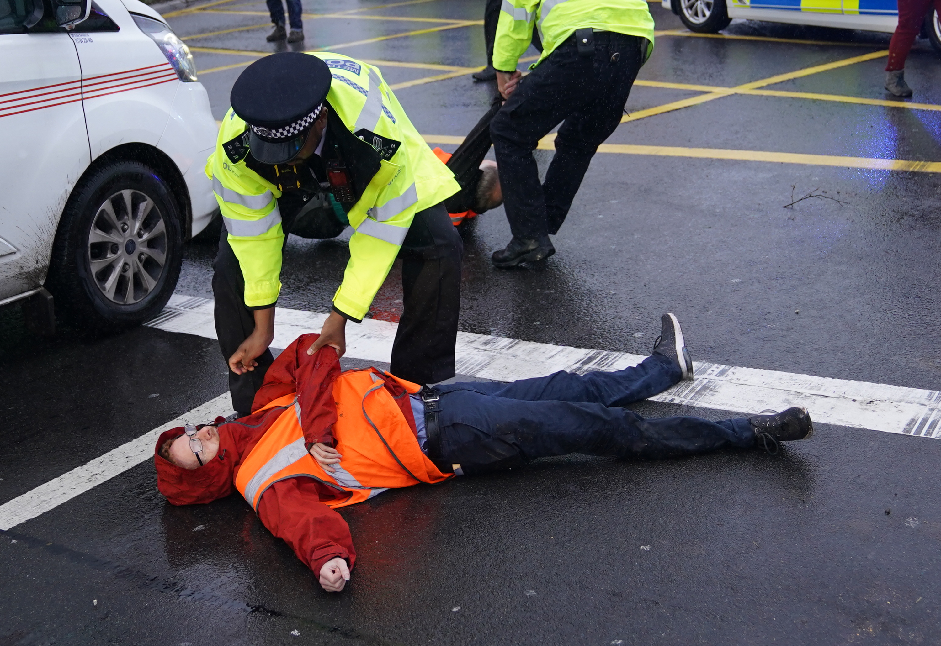 <p>A police officer detains a protester from Insulate Britain occupying a roundabout leading from the M25 motorway to Heathrow Airport in London. Picture date: Monday September 27, 2021.</p>
