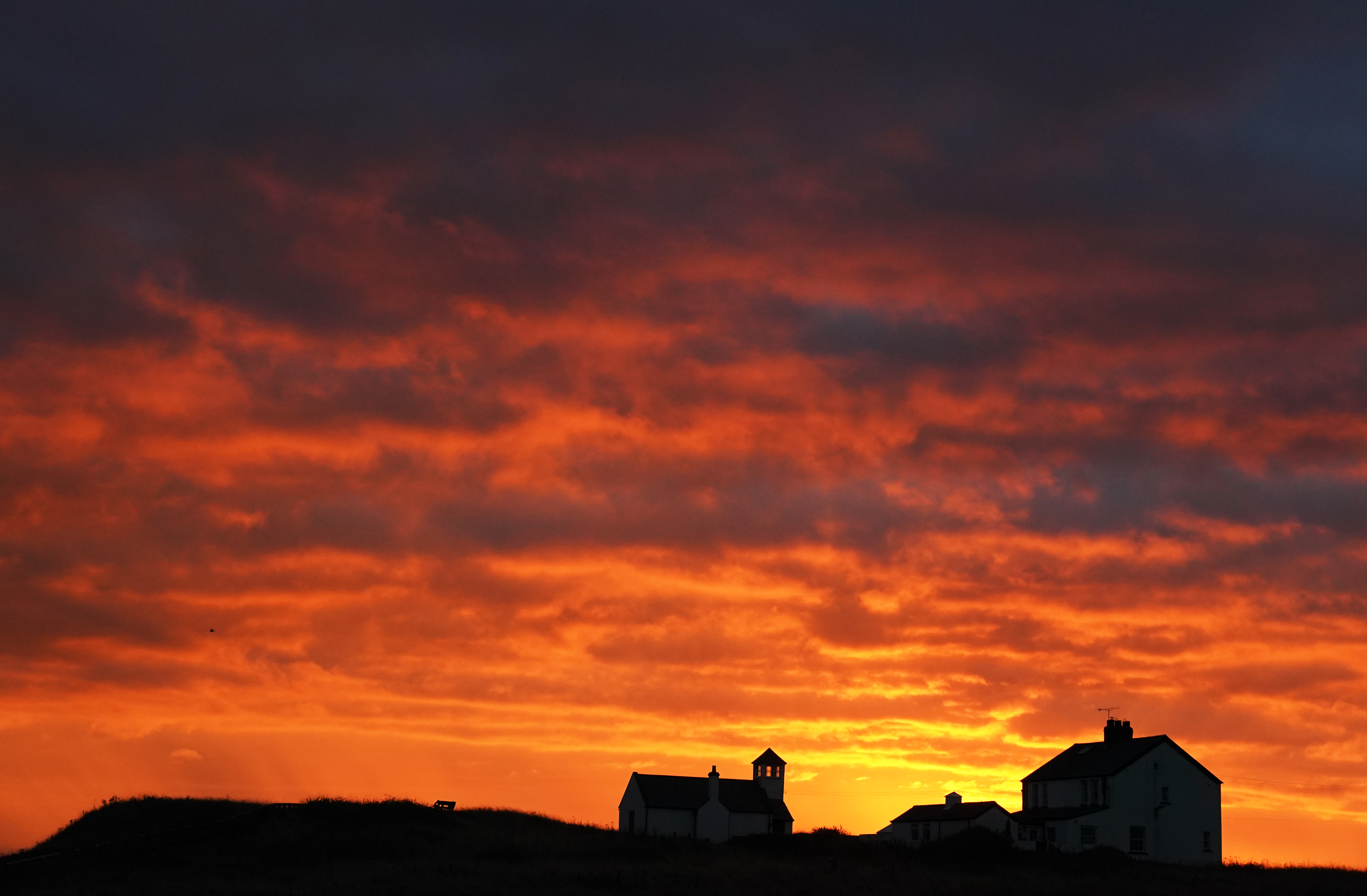 <p>The sky lit up before sunrise over the Watch House Museum in Seaton Sluice, Northumberland. Picture date: Monday September 27, 2021.</p>