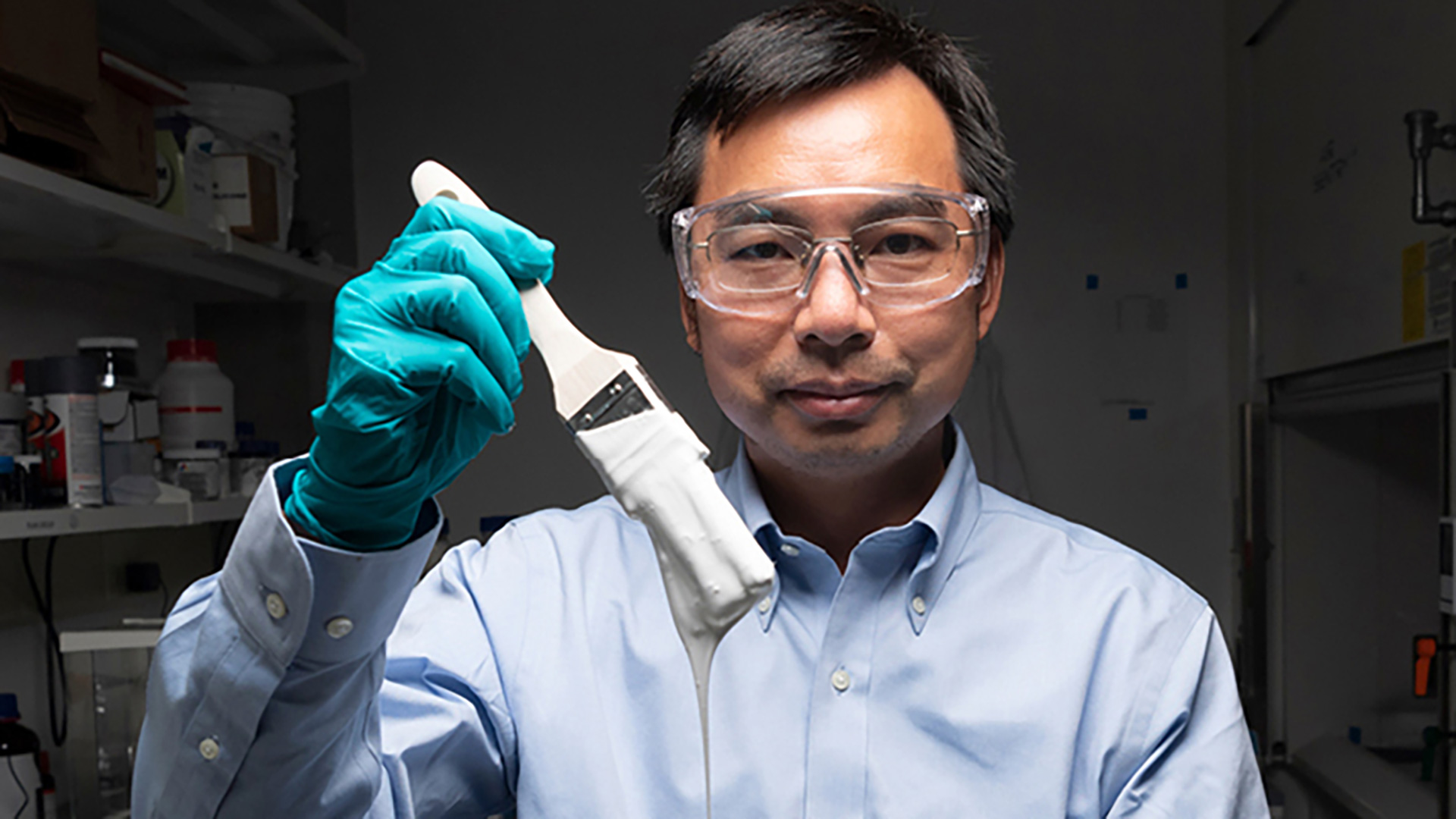 Purdue University professor Xiulin Ruan holds a brush with the whitest-ever paint.