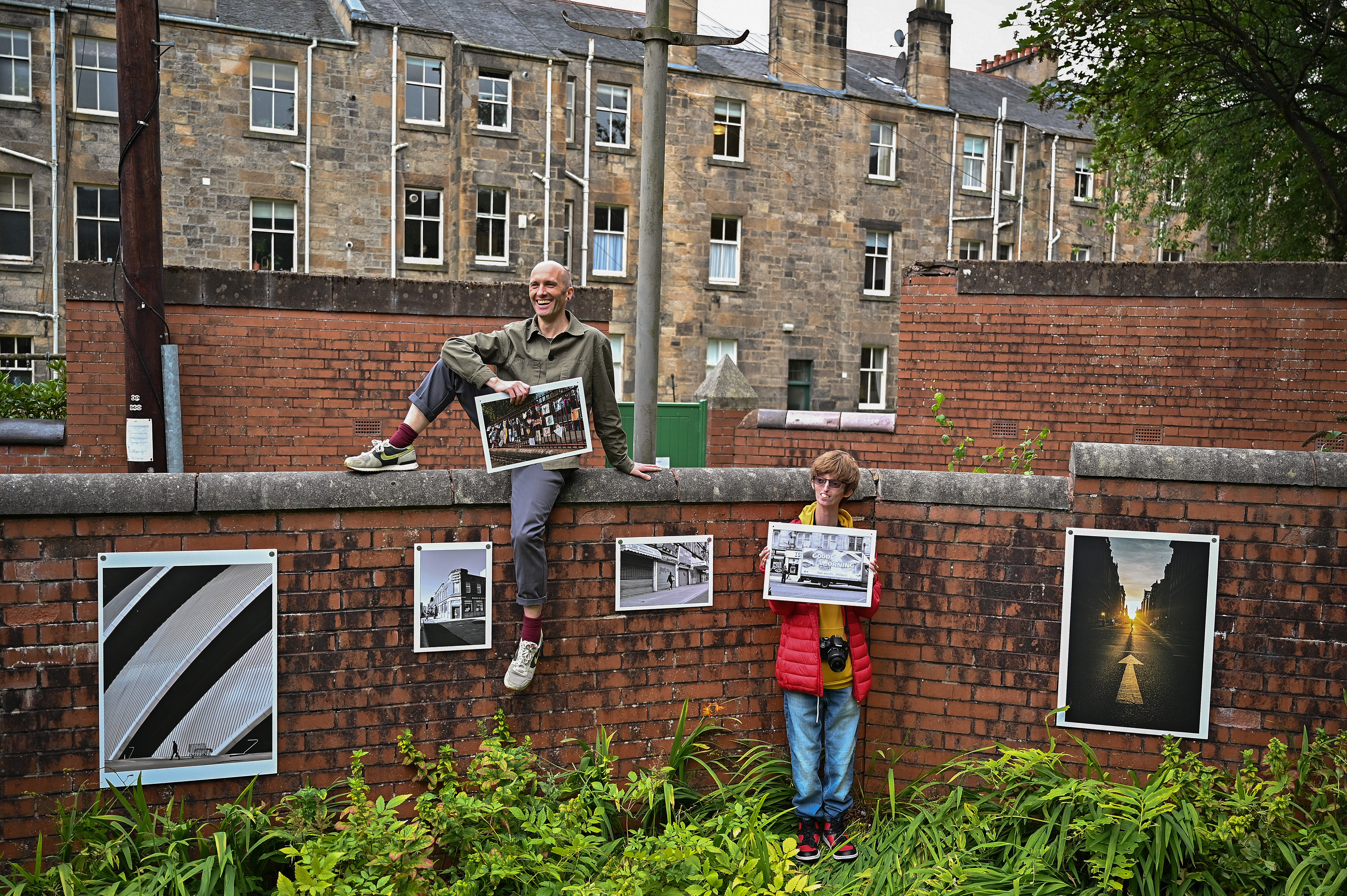 """<p>GLASGOW, SCOTLAND - SEPTEMBER 17: Brian Hartley and Dylan Lombard (R) pose beside their photographic exhibition in a tenement garden on September 17, 2021 in Glasgow, Scotland. """"Stills of a Lockdown City"""" features images taken during the 2020 coronavirus lockdown by Glasgow-based artist Brian Hartley and 18-year-old Dylan Lombard, and aims to offer """"a perspective that allows us to make more sense of the world"""". It will take place on September 18 and 19, 2021. (Photo by Jeff J Mitchell/Getty Images)</p>"""