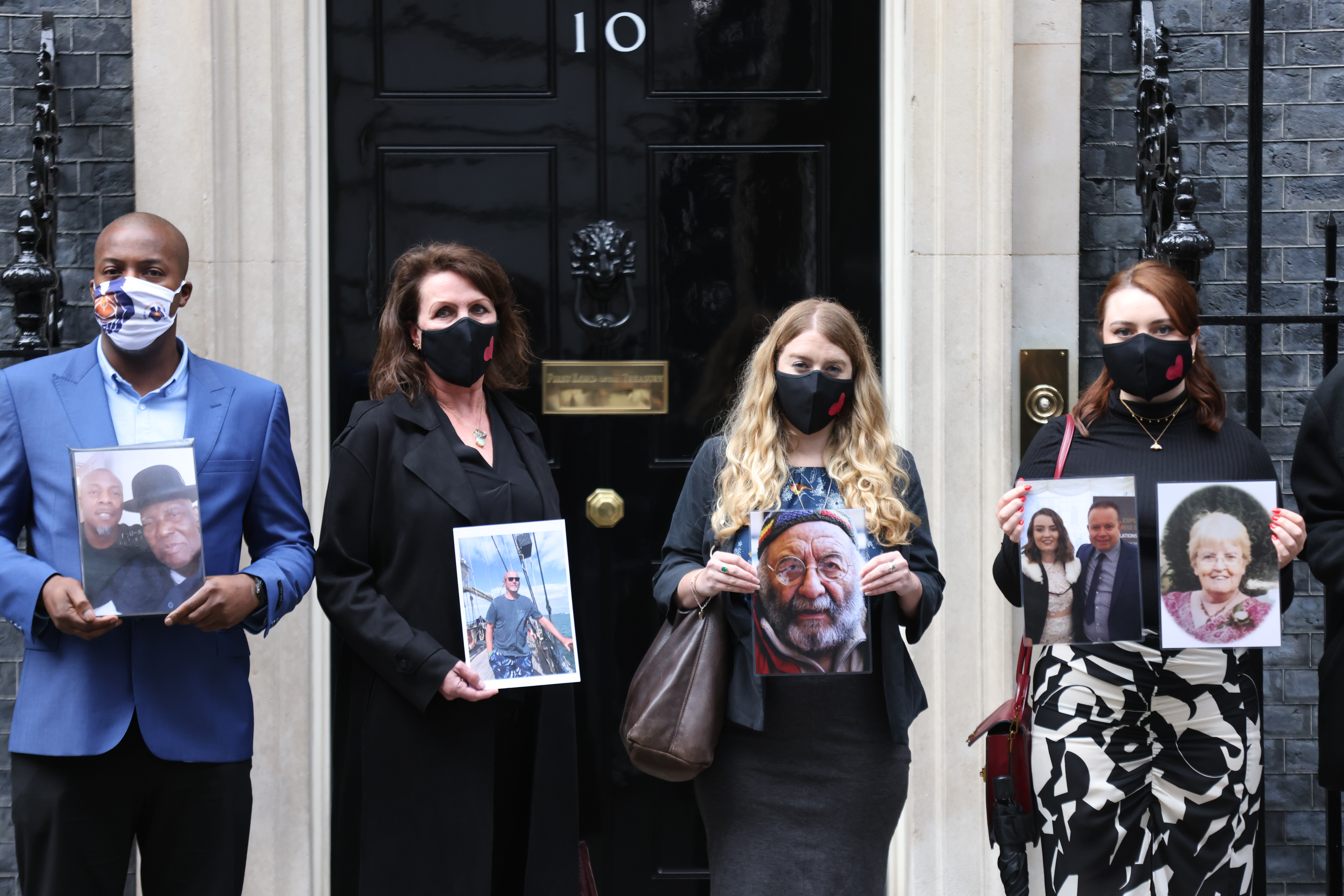 <p>Members of the Covid-19 Bereaved Families for Justice group holding photos of loved ones outside 10 Downing Street, London, after their private meeting with Prime Minister Boris Johnson, 398 days after he first promised to do so. Picture date: Tuesday September 28, 2021.</p>