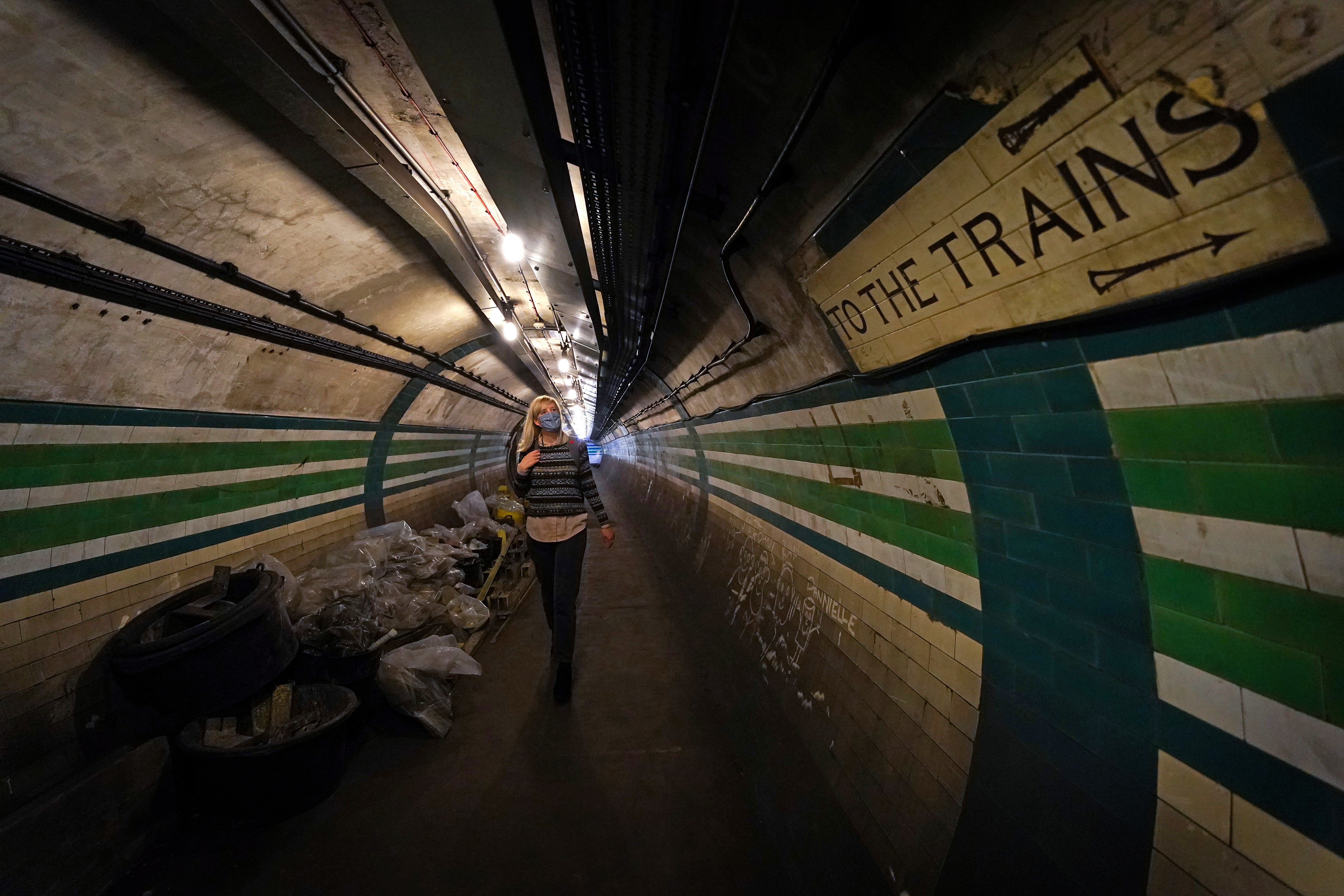 <p>A member of Transport Museum staff walks through a disused passageway during a tour at the Piccadilly Circus disused tube station in London. London Transport Museum are re-starting in-person Hidden London tours of disused tube stations for the first time since the pandemic. Picture date: Tuesday September 28, 2021.</p>