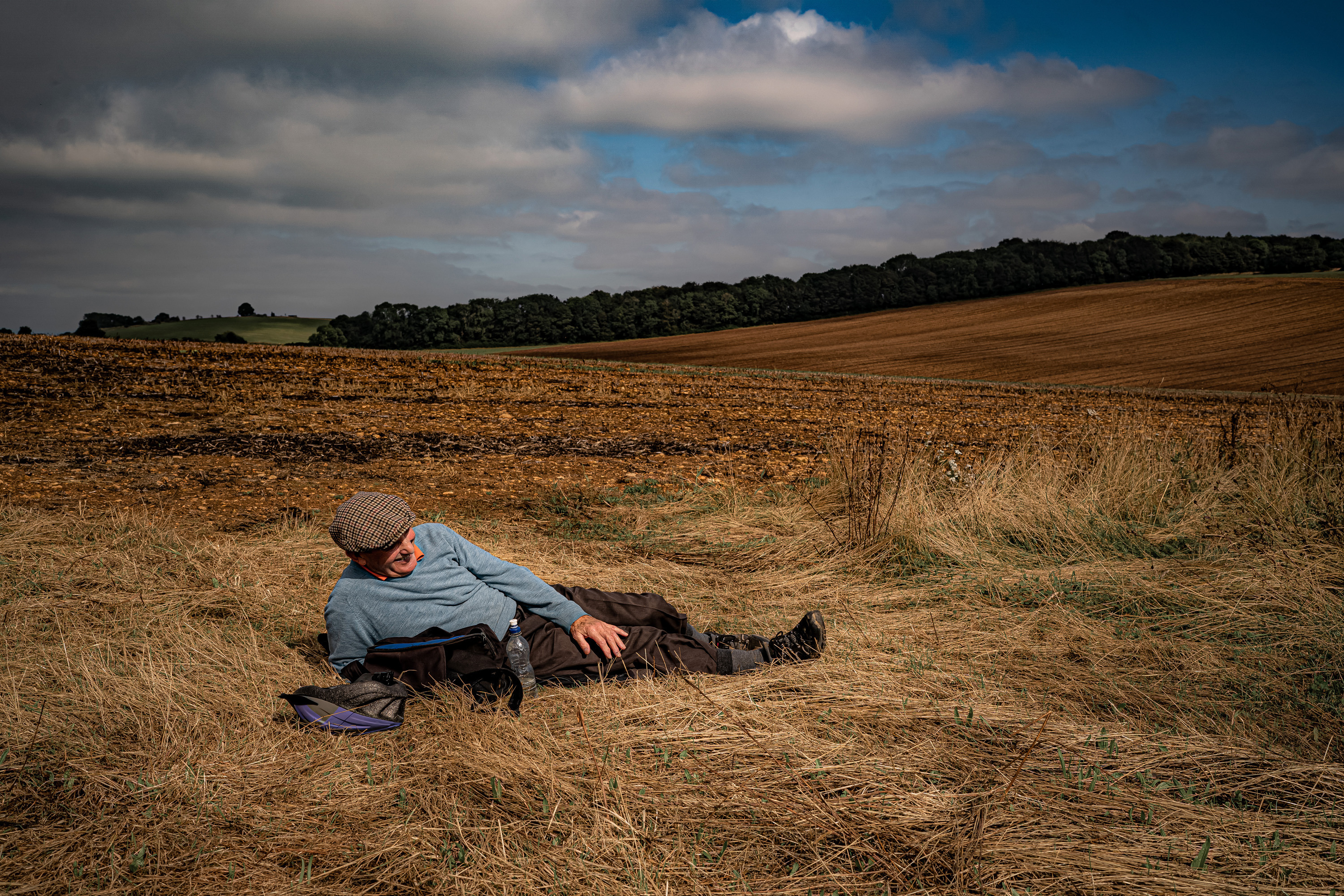 <p>A man takes a rest in a stubble-burned field on a sunny day, where low fluffy clouds cast shadows on the Cotswold landscape near Snowshill. Picture date: Wednesday September 15, 2021.</p>
