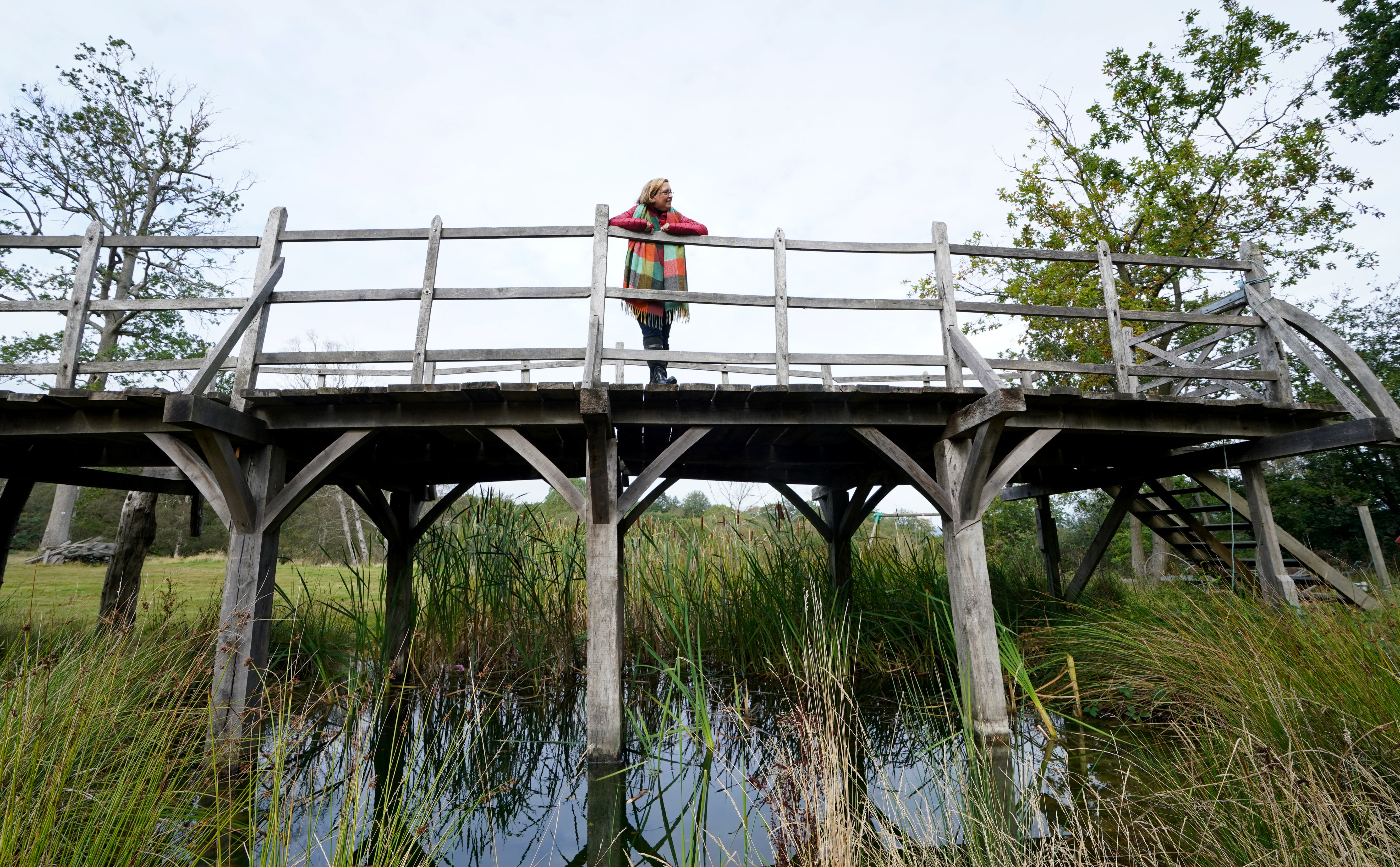 <p>Silke Lohmann of Summers Place Auctions stands on the original Poohsticks Bridge in Ashdown Forest in Kent. The bridge, which featured in A.A. Milne's Winnie the Pooh books and E.H. Shepard's illustrations, was replaced in 1999, but the original has been fully restored and goes up for sale at the auction house on October 5, for an estimate of �40,000 - �60,000. Picture date: Thursday September 30, 2021.</p>