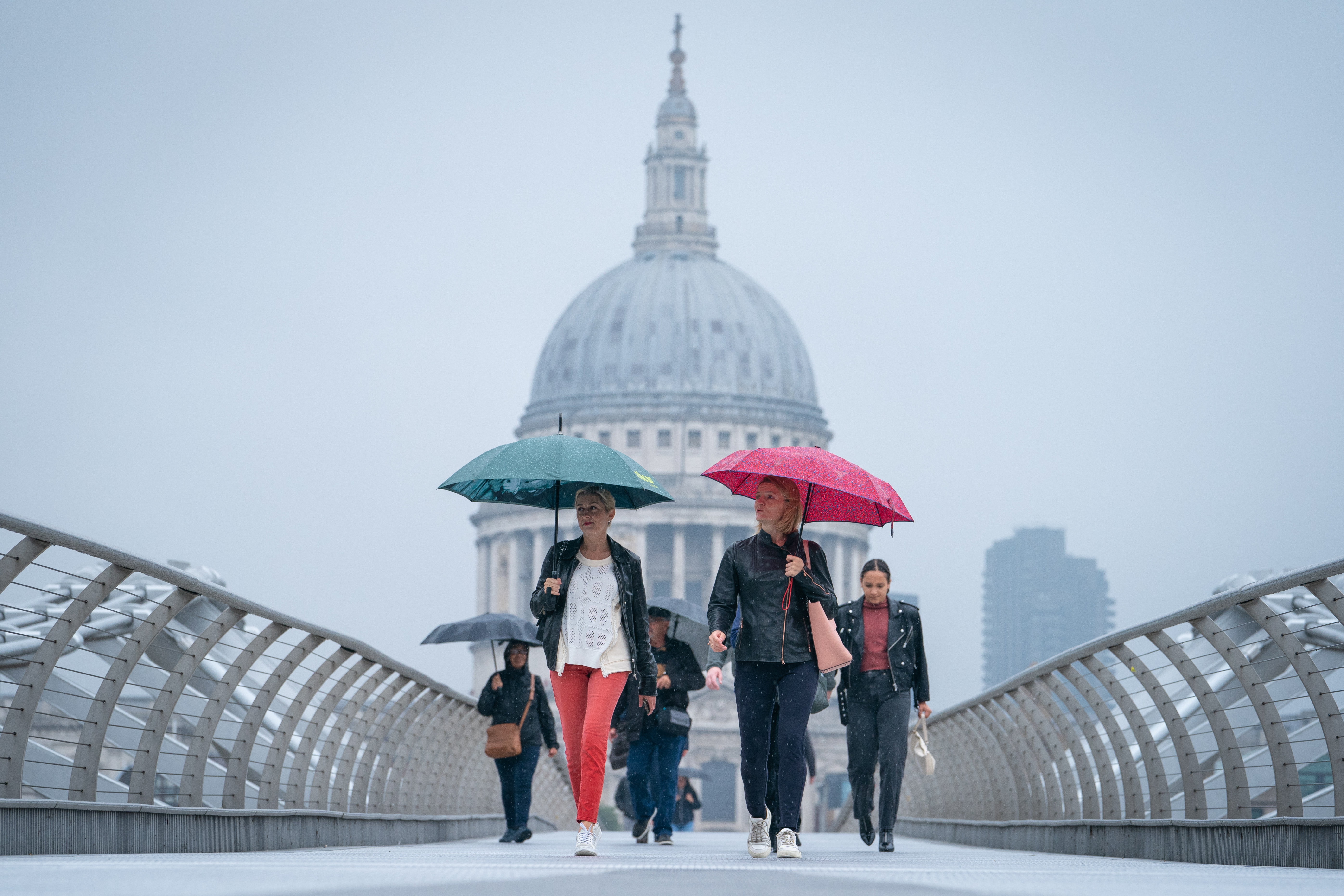 <p>People shelter from the rain under umbrellas as they cross the Millennium Bridge near St Paul's Cathedral, in central London. Picture date: Tuesday September 14, 2021.</p>